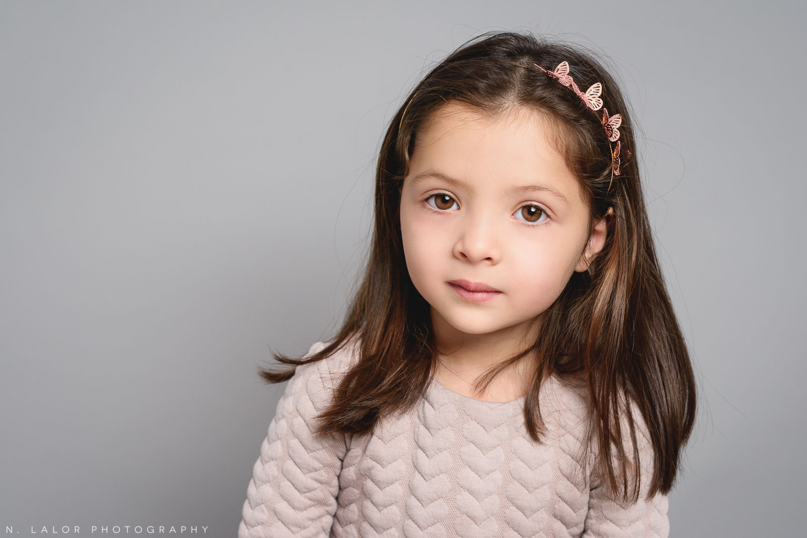 Non-smiling photo of a little girl. Studio portrait by N. Lalor Photography in Greenwich, Connecticut.