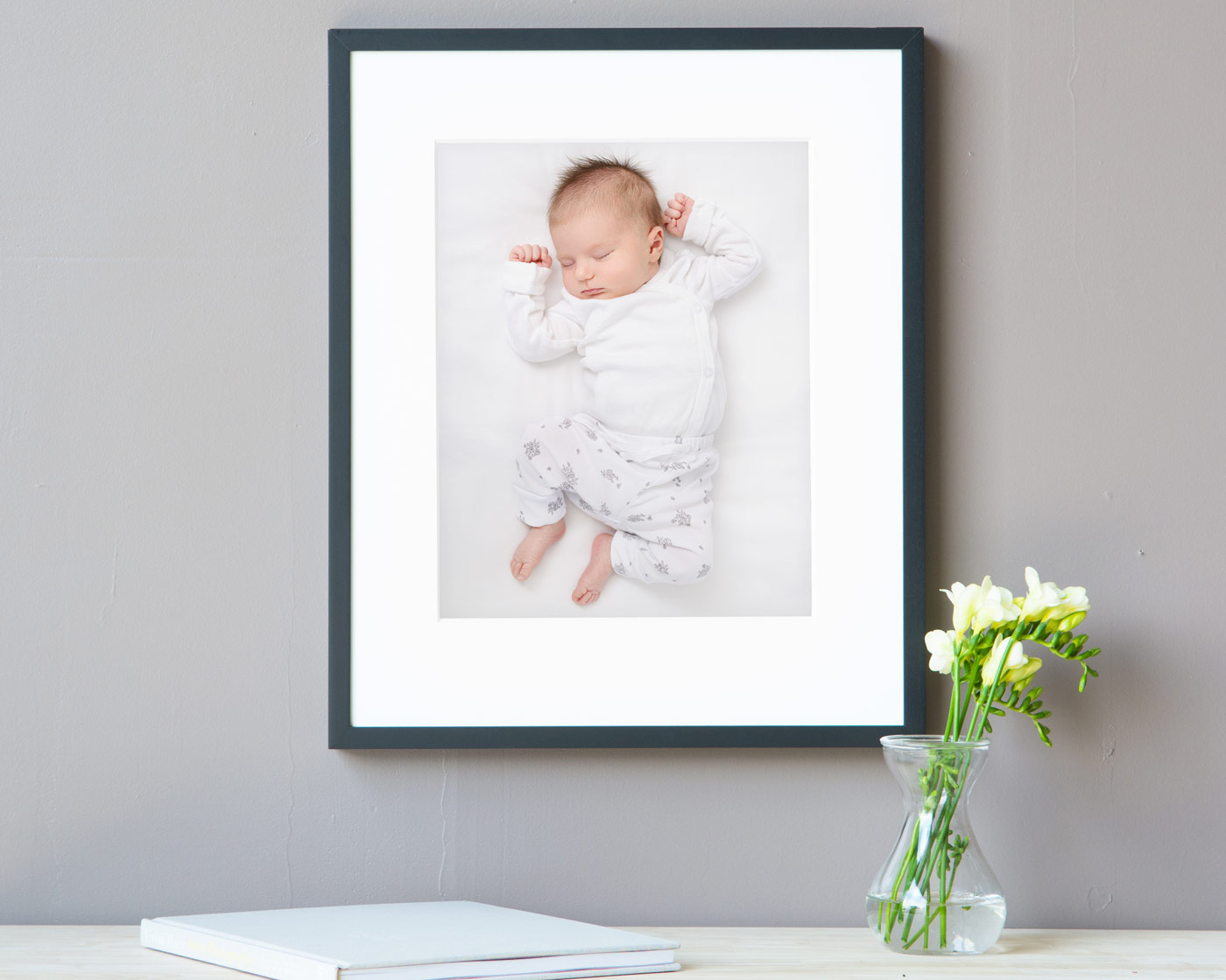 "Image of an 11x14"" framed print of a newborn baby, in a black frame."