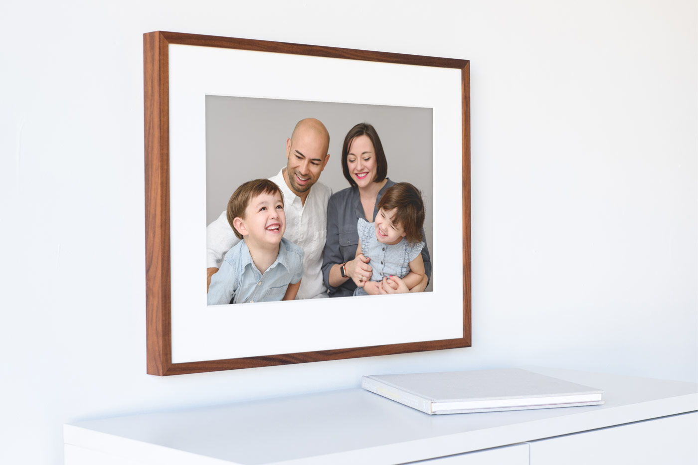 "Image of a 16x24"" framed print of a family in a simple white interior setting."