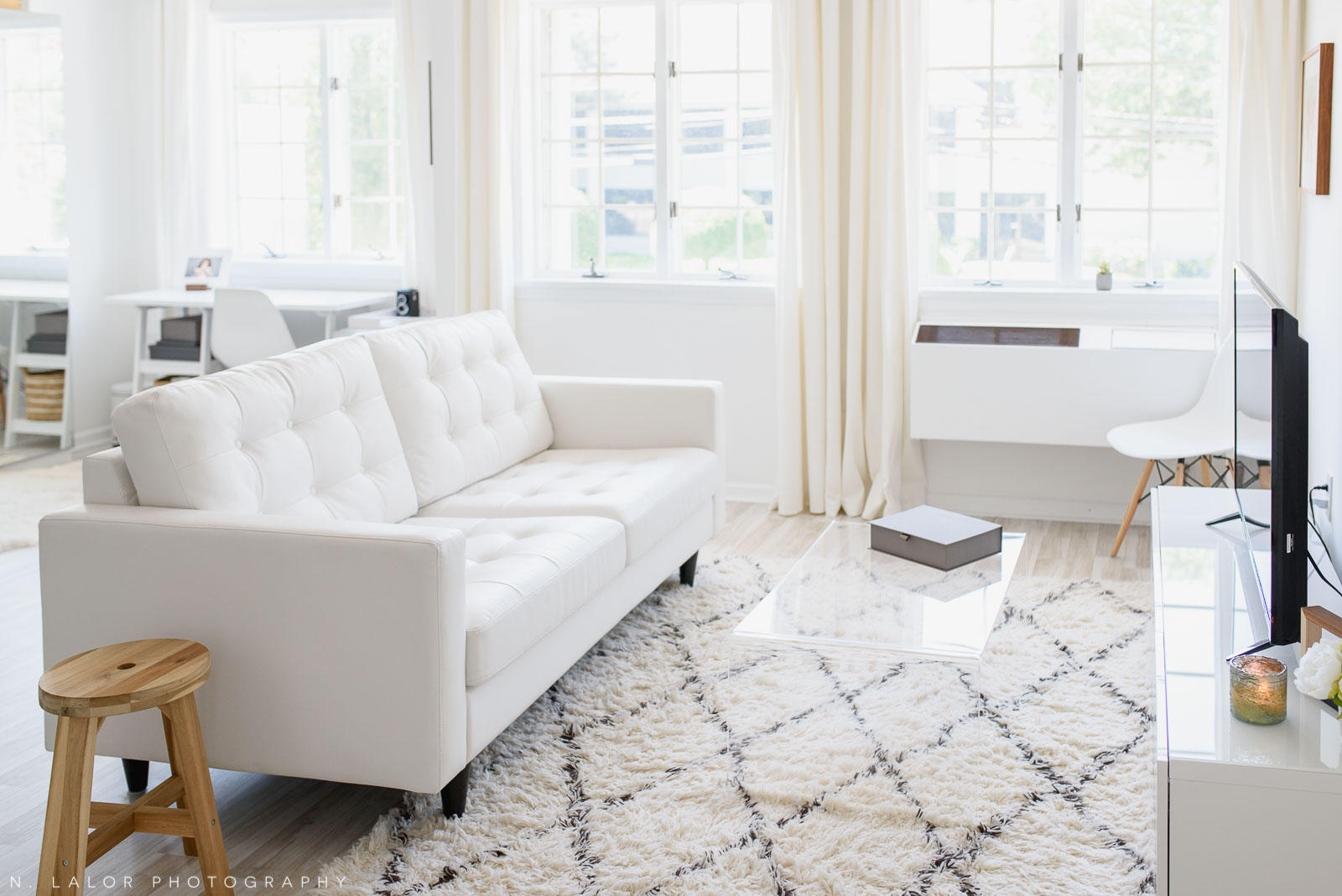 N. Lalor Photography Studio - client meeting area with white couch and coffee table.