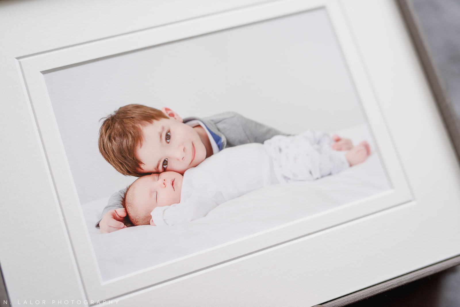 Photograph of older brother and his baby sister in a simple and clean style. Studio portrait by N. Lalor Photography in Greenwich, Connecticut.