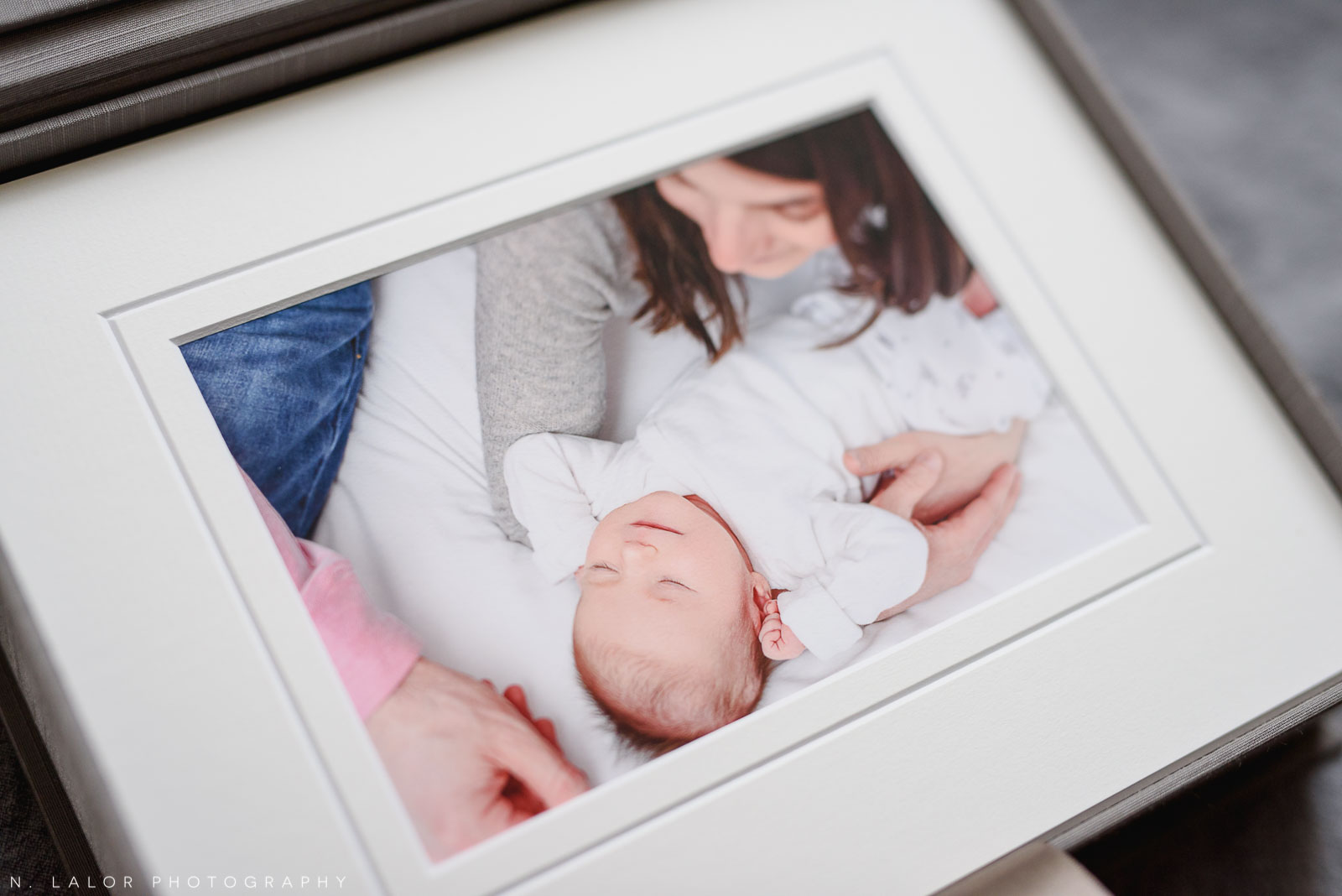 Image of a candid newborn portrait, printed and matted. Studio portrait by N. Lalor Photography in Greenwich, Connecticut.