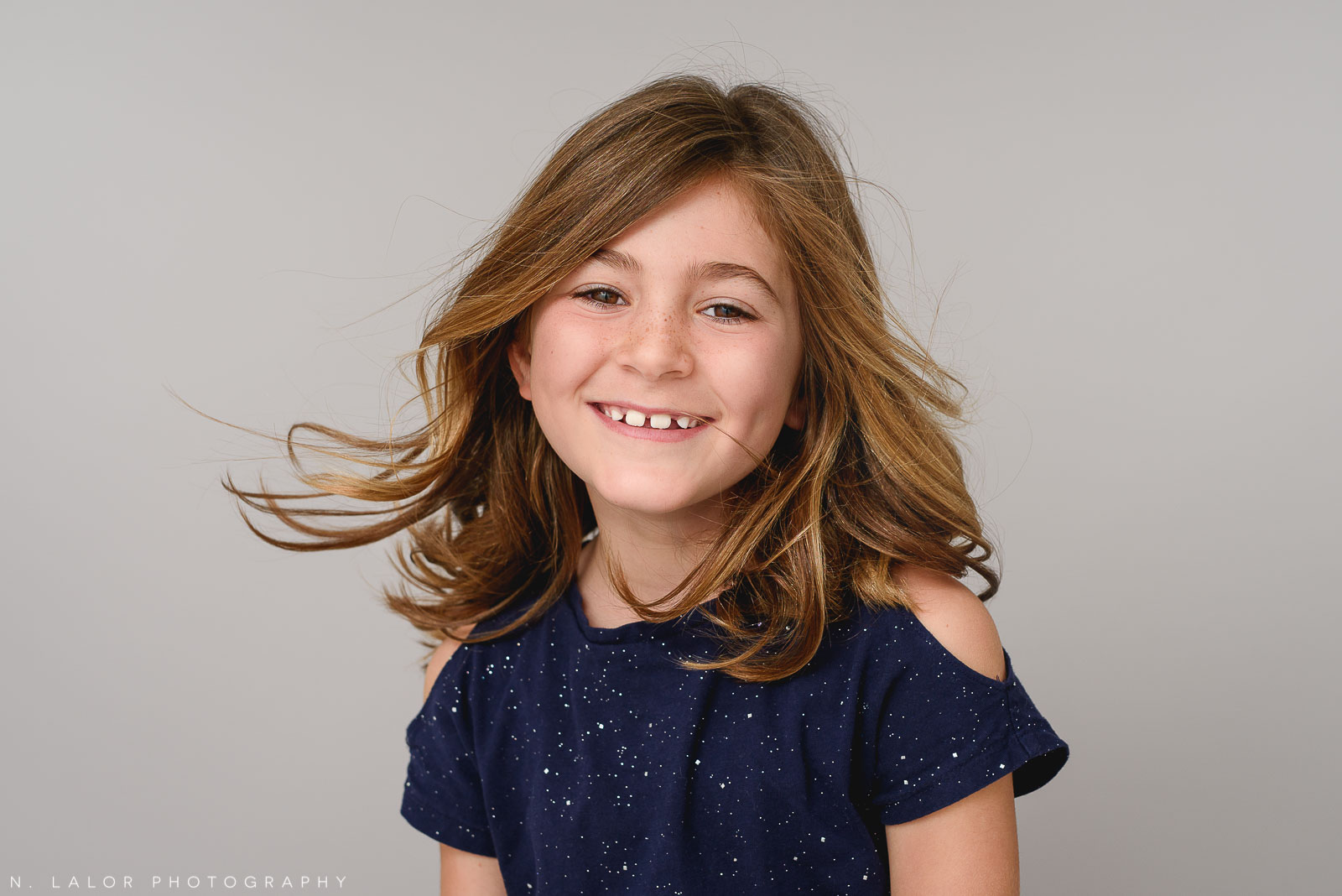 Image of a happy girl with wind blowing her hair.Studio portrait by N. Lalor Photography in Greenwich, Connecticut.