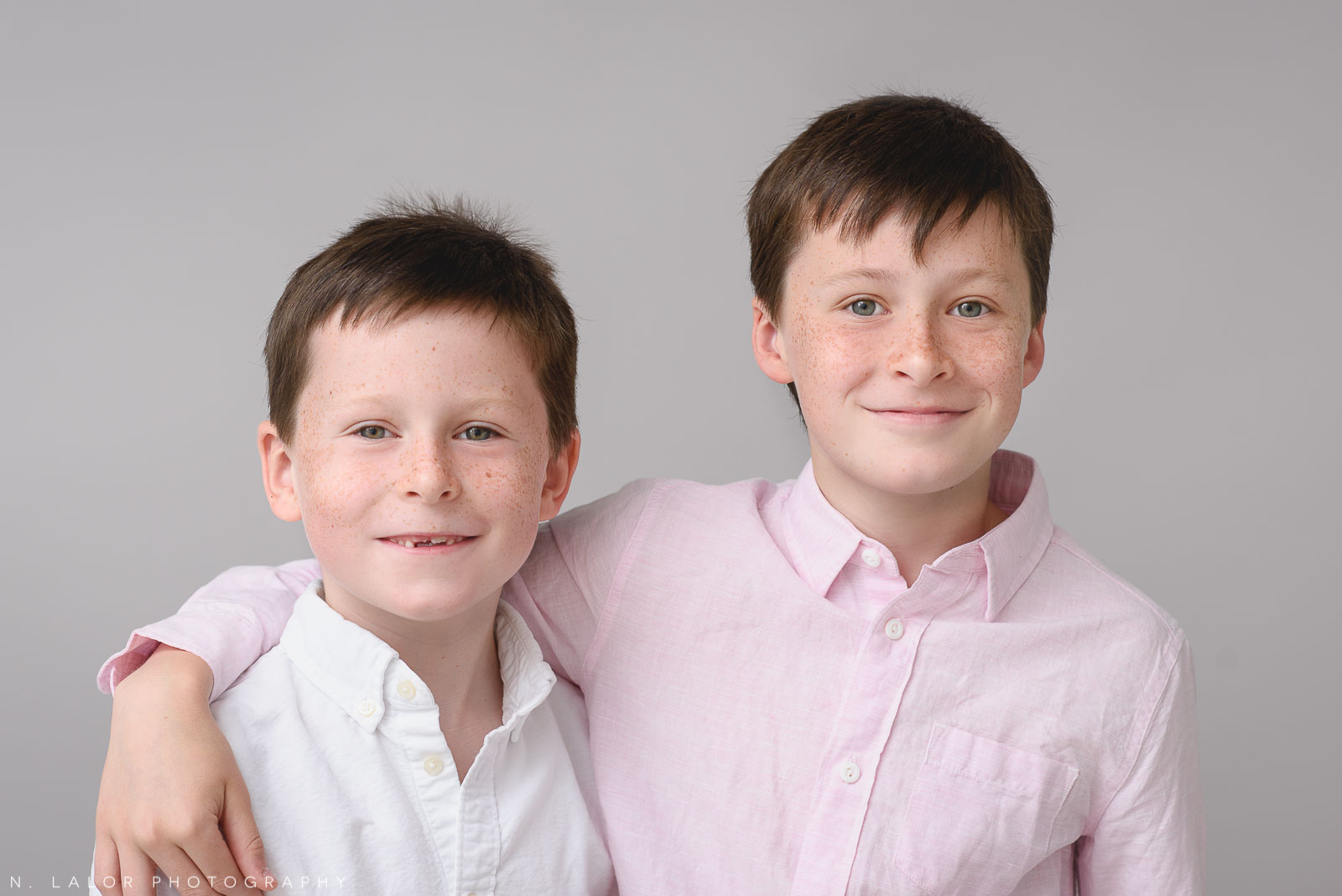 Image of two brothers being happy together.Studio portrait by N. Lalor Photography in Greenwich, Connecticut.