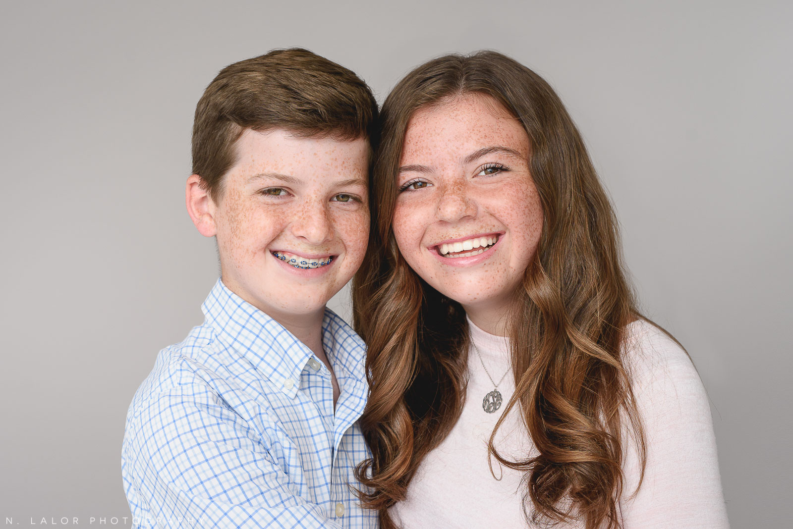 Image of a brother and sister, laughing.Studio portrait by N. Lalor Photography in Greenwich, Connecticut.