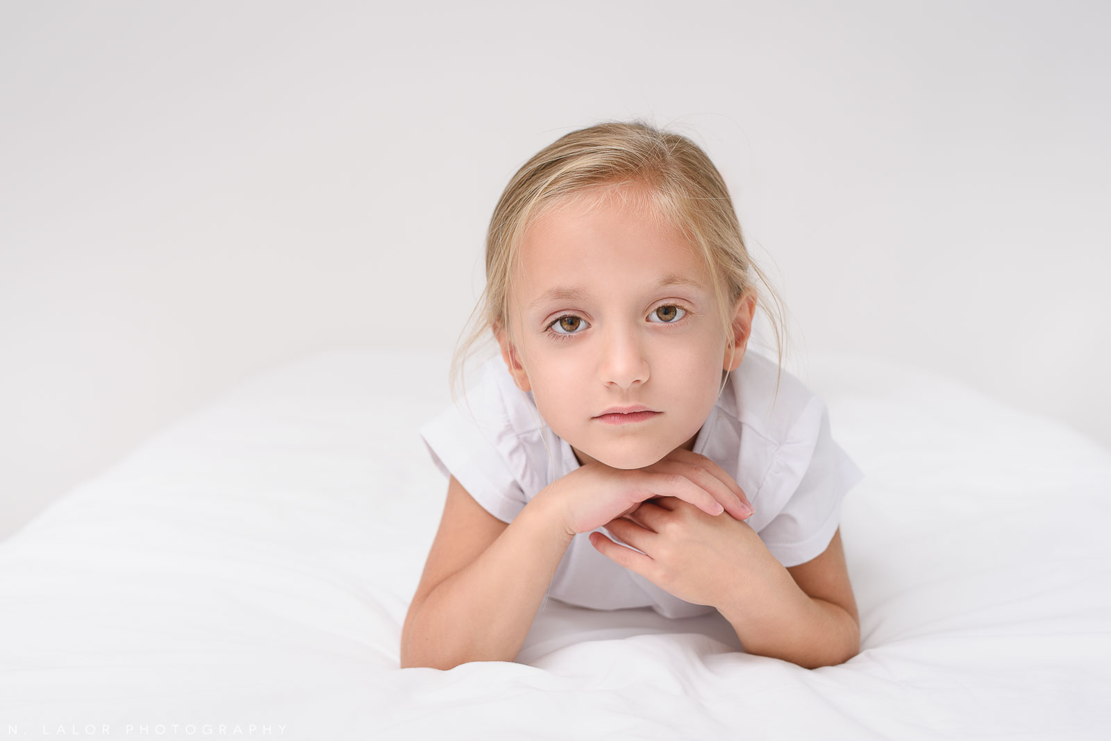 Image of a 6 year old girl on a white bed. Studio portrait by N. Lalor Photography in Greenwich Connecticut.