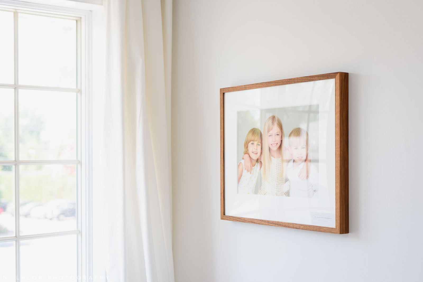 Image of a framed portrait on a wall. Photos by N. Lalor Photography, Studio located in Greenwich Connecticut.