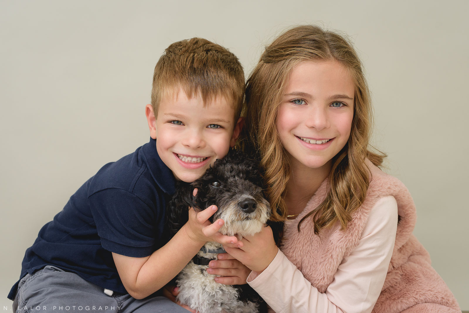 Image of two children with their dog. Portrait by N. Lalor Photography, Studio located in Greenwich Connecticut.