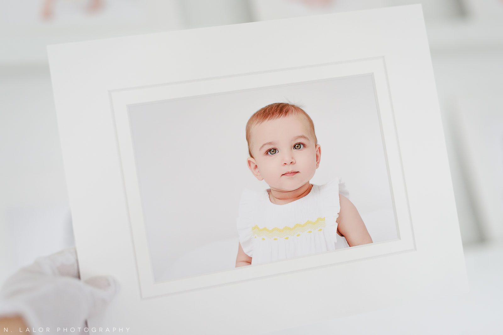 Image of an archival museum-quality print of a baby girl. Portrait by N. Lalor Photography, Studio located in Greenwich Connecticut.