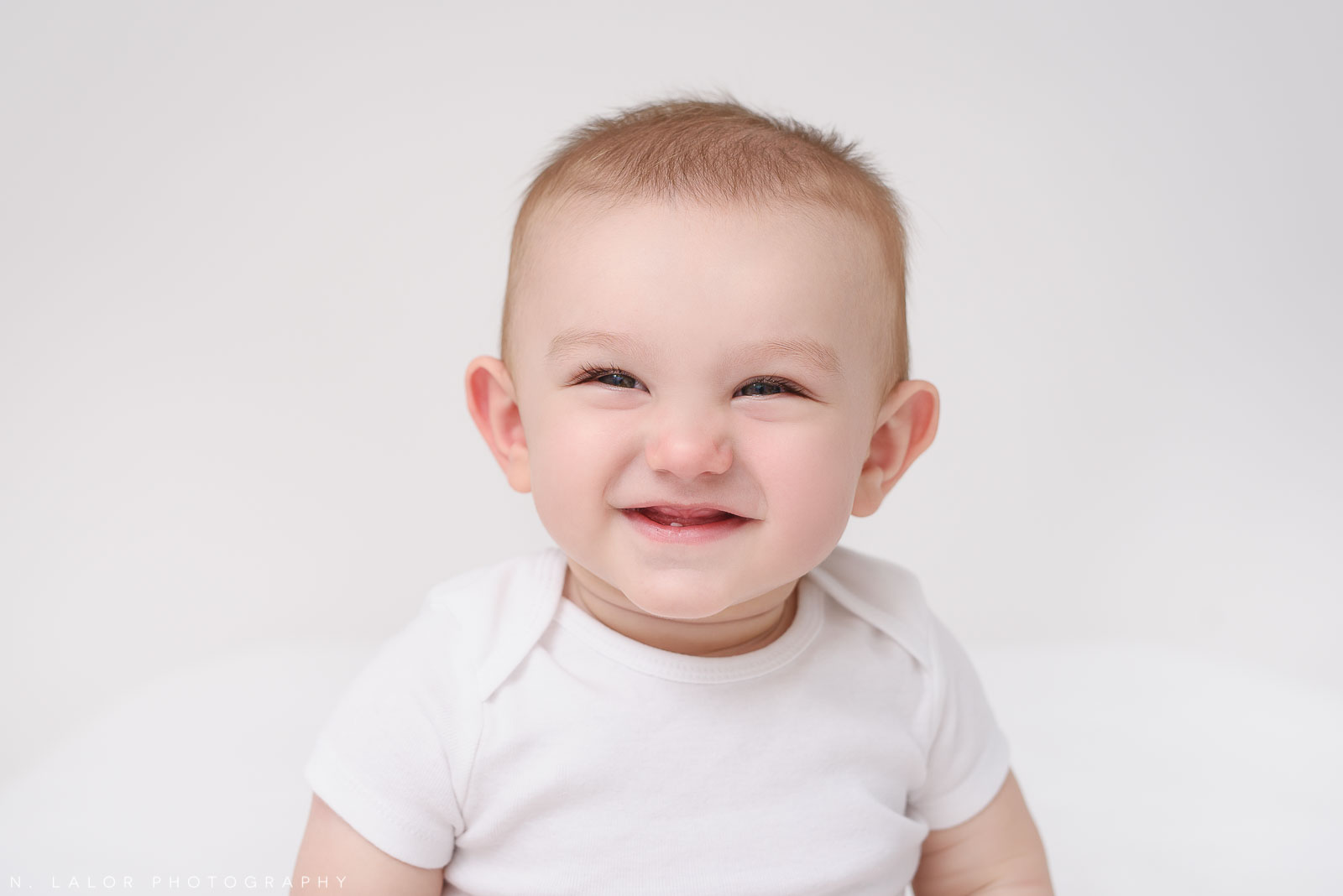 Image of an adorable baby smiling with one little tooth popping through. Studio portrait by N. Lalor Photography in Greenwich, Connecticut.