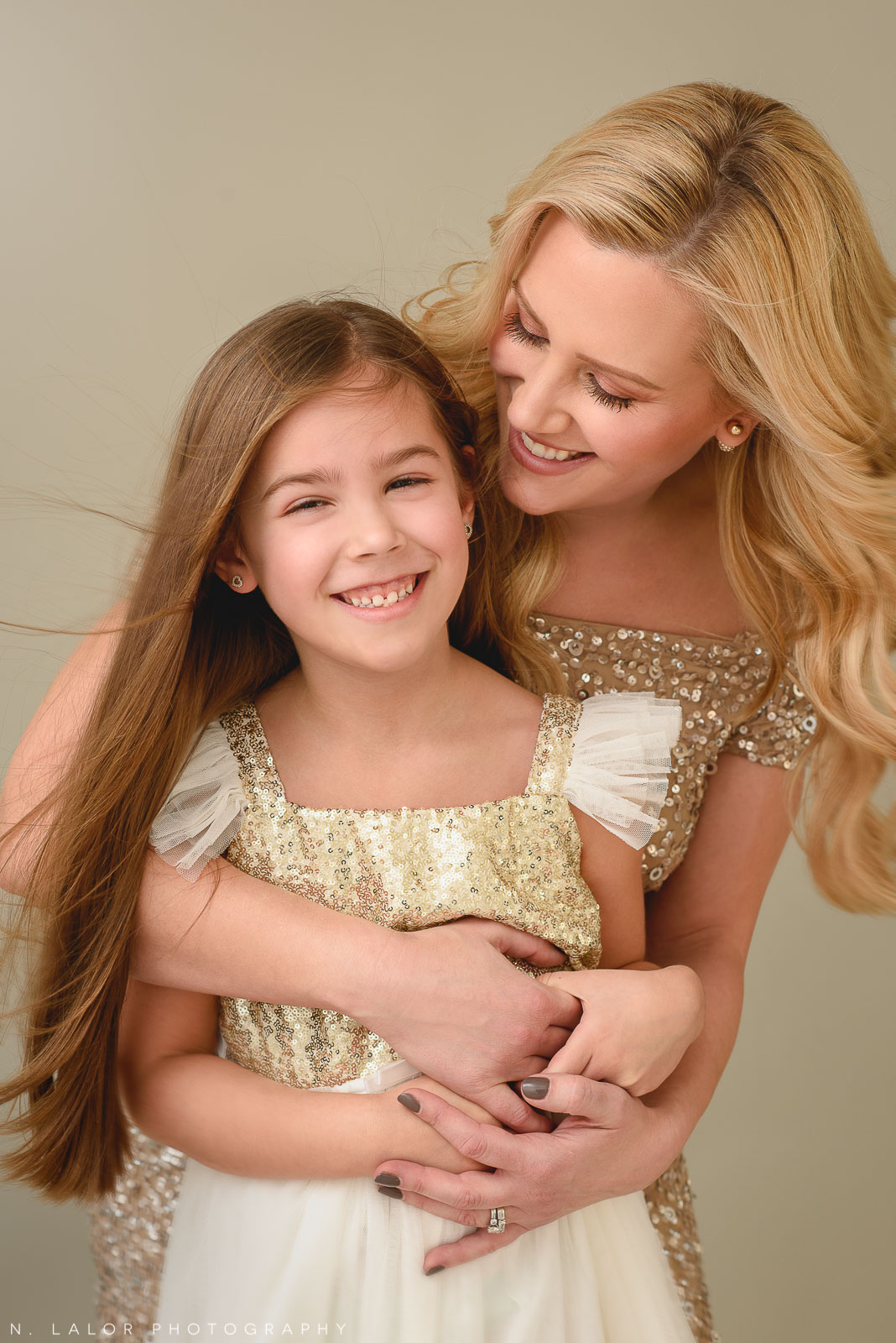Image of a mother and daughter laughing together. Studio portrait by N. Lalor Photography in Greenwich, Connecticut.