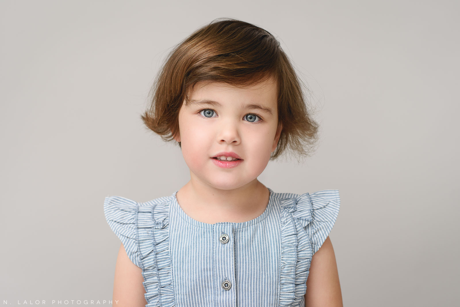 Image of a young girl looking at the camera. Portrait by N. Lalor Photography in Greenwich, Connecticut.