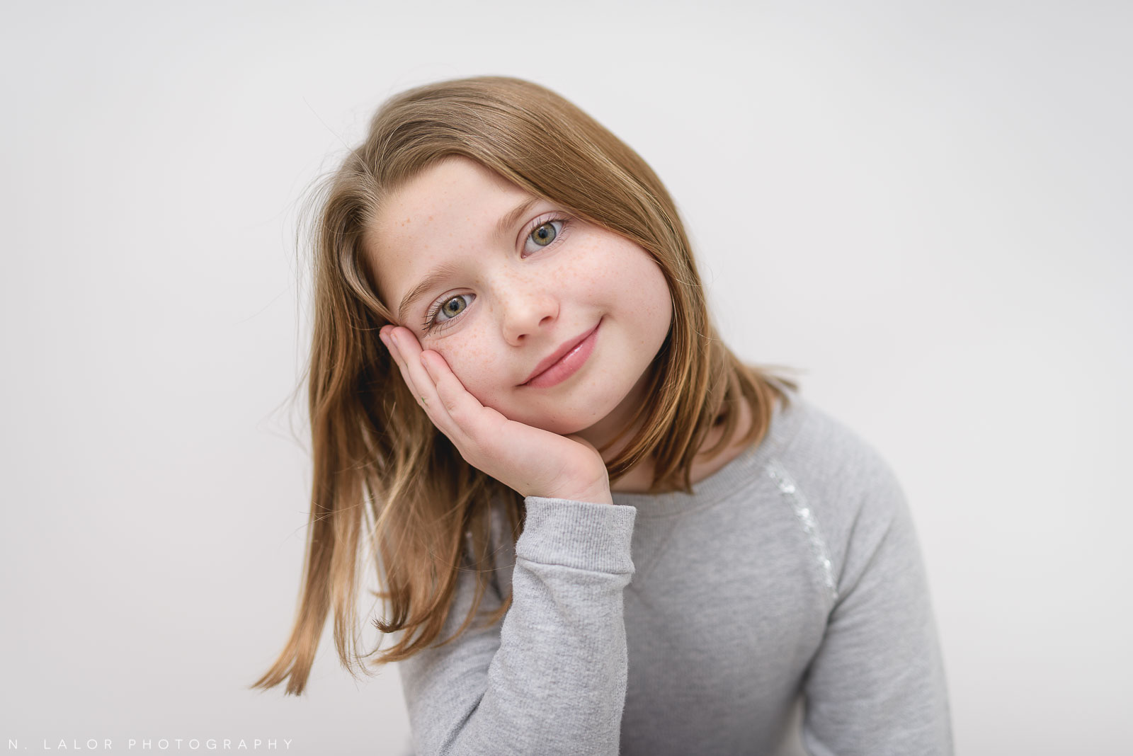 Simple and bright image of an 8-year old girl. Studio portrait by N. Lalor Photography in Greenwich Connecticut.