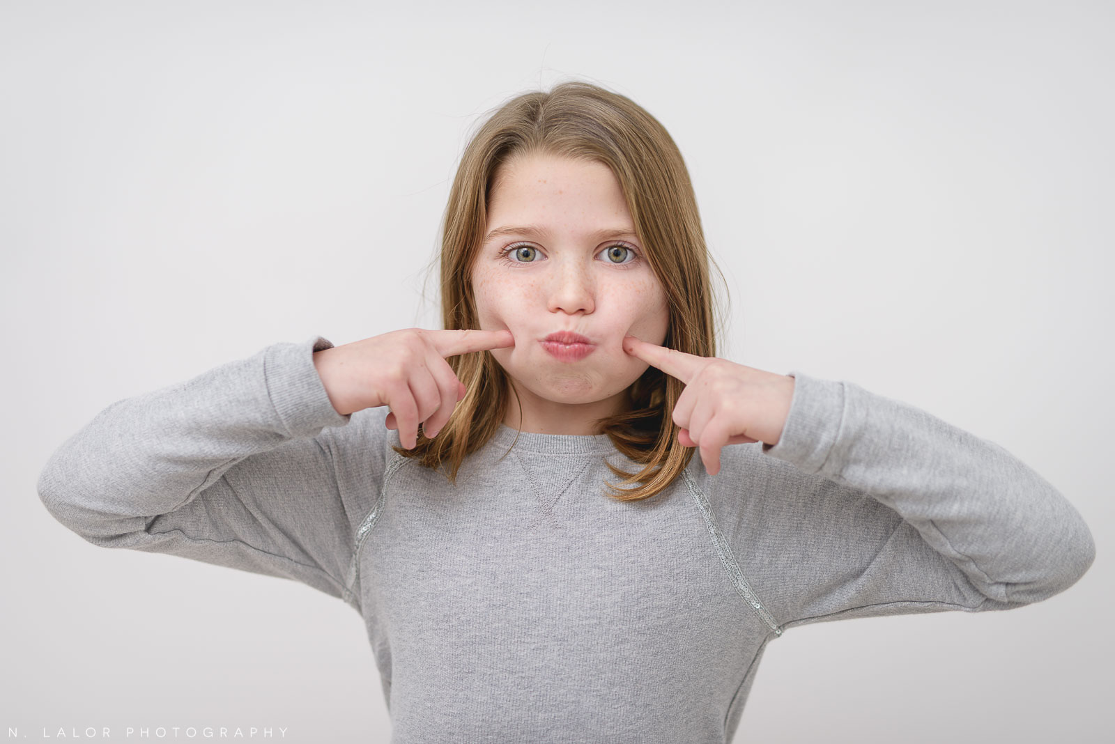Funny face image of an 8-year old girl. Studio portrait by N. Lalor Photography in Greenwich Connecticut.