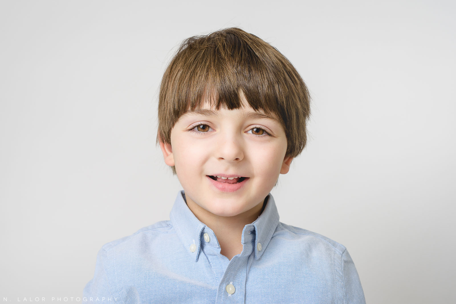 Image of a 5-year old boy smiling. Studio portrait by N. Lalor Photography in Greenwich, Connecticut.