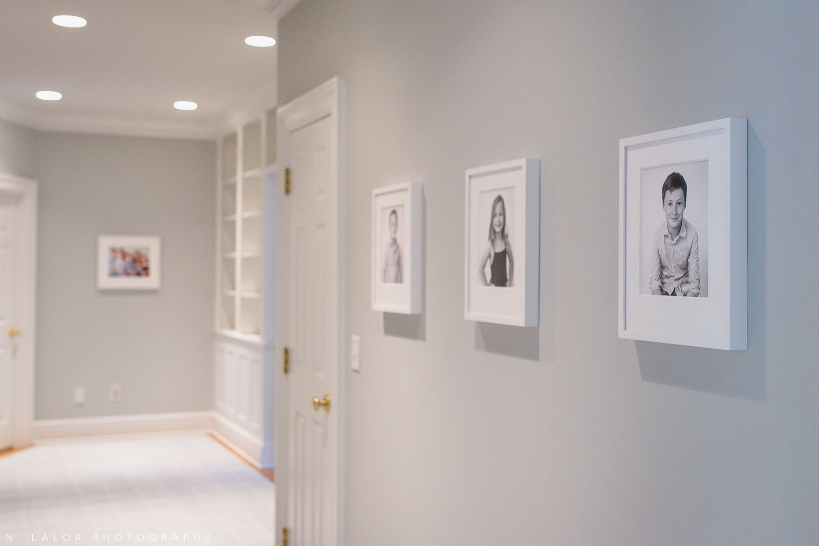 Image of a home hallway lined with printed and framed family photographs. Studio portrait by N. Lalor Photography in Greenwich, Connecticut.