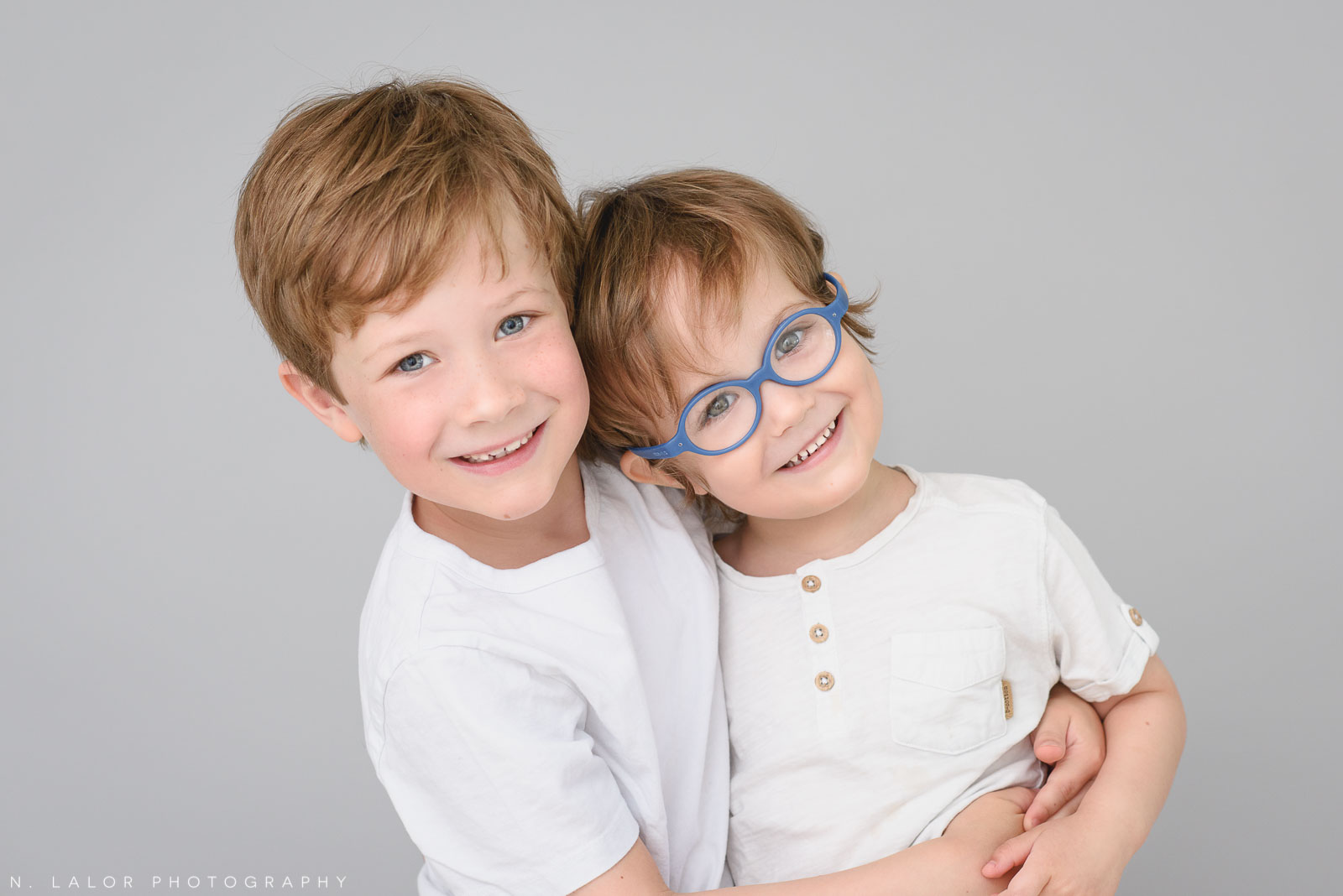 Photography of two brothers, smiling. Studio portrait by N. Lalor Photography in Greenwich, Connecticut.