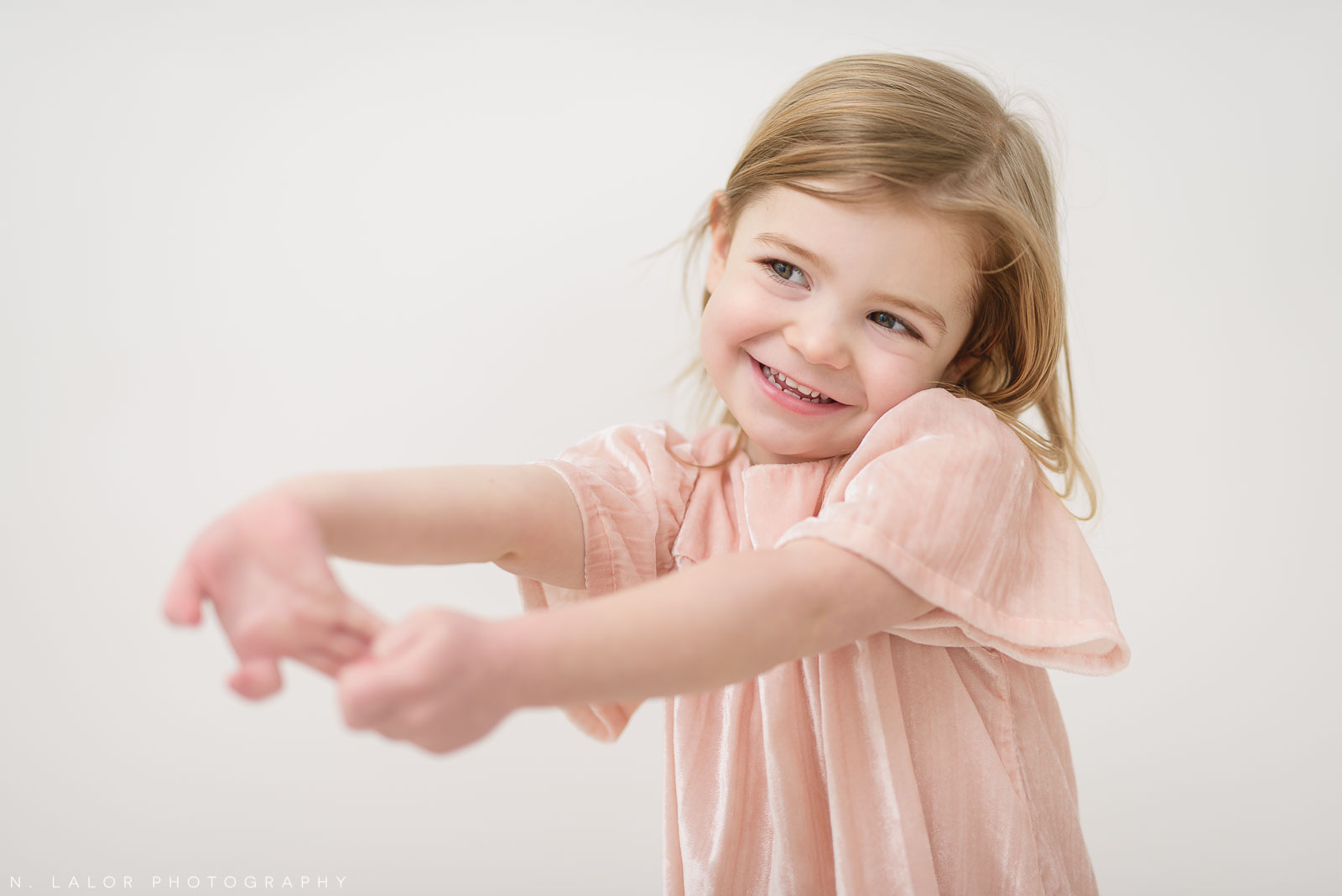 Image of an active preschooler, showing that she doesn't need to stay still in a photograph. Studio portrait by N. Lalor Photography in Greenwich, Connecticut.