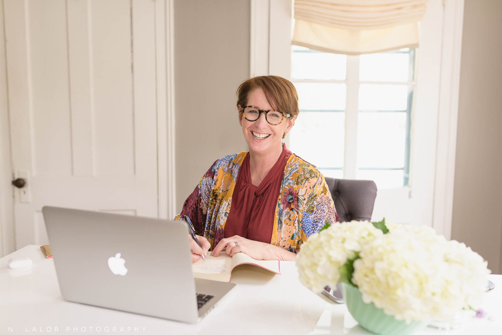 Image of a woman writing in her notebook while working in a home office. Portrait by N. Lalor Photography, Westport, Connecticut.