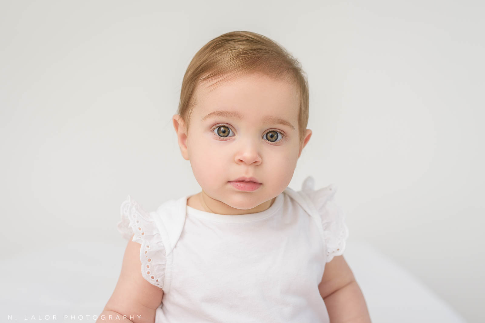 Image of a baby girl looking at the camera. Studio baby portrait by N. Lalor Photography in Greenwich Connecticut.
