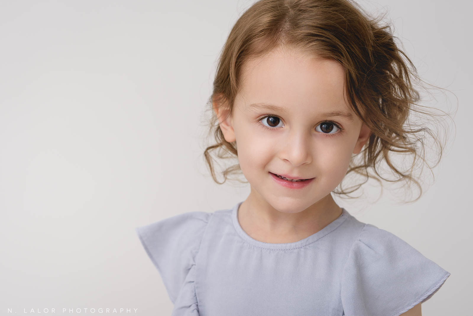 Image of a girl looking at the camera. Studio child portrait by N. Lalor Photography in Greenwich Connecticut.