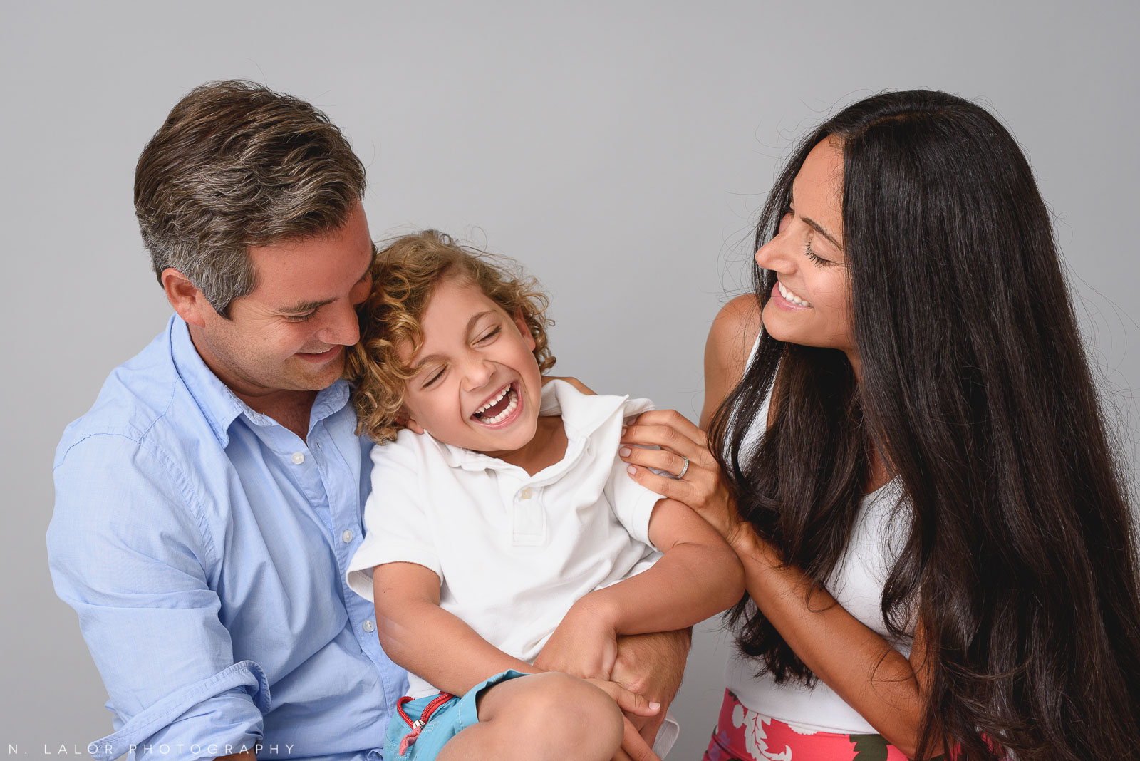 Image of Mom and Dad with their young boy, laughing. Studio family portrait by N. Lalor Photography in Greenwich, CT.
