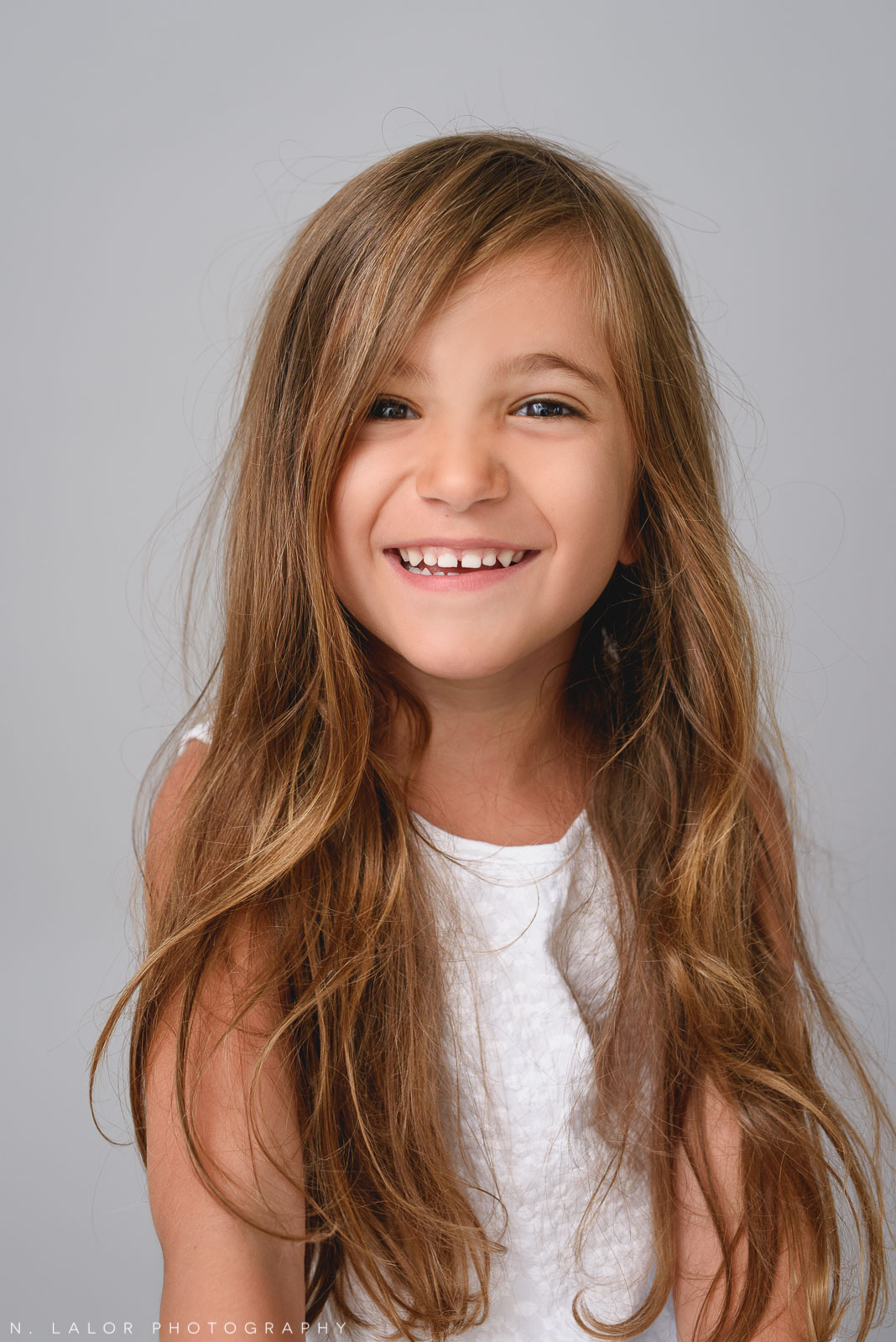 Image of a happy smiling girl with a great summer tan. Studio family portrait by N. Lalor Photography in Greenwich, CT.