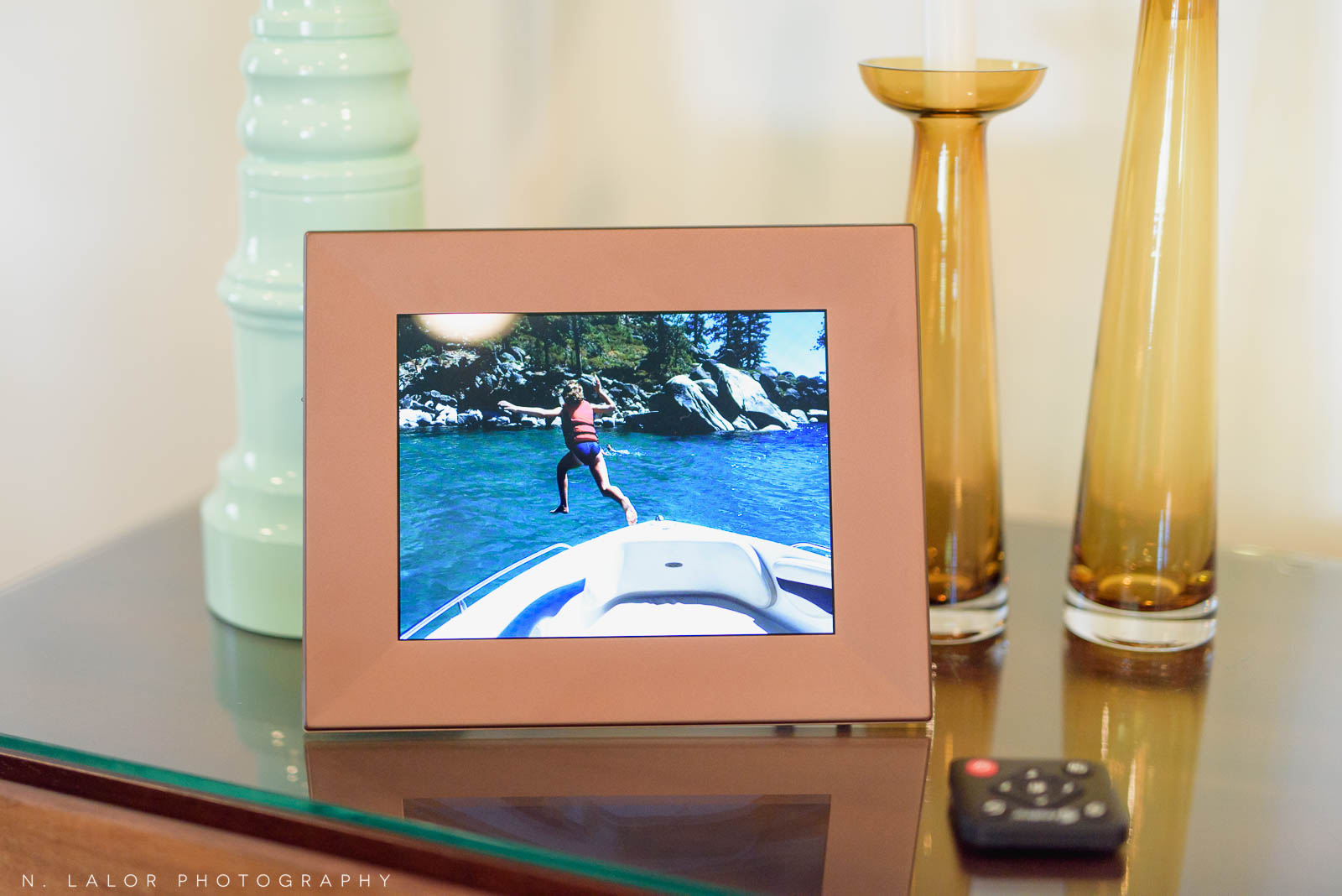 Image of digital frame with vacation photo on table. Photography by N. Lalor Photography. Studio in Greenwich, Connecticut.