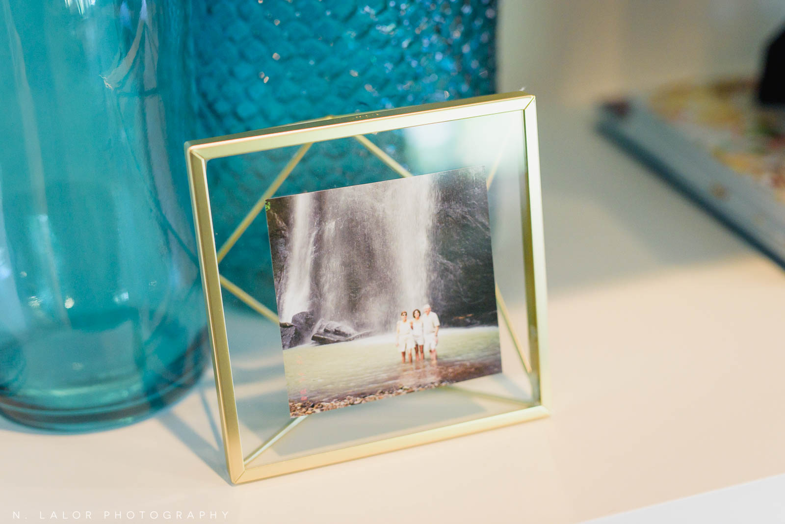 Image of vacation photo in beautiful glass frame on table. Photography by N. Lalor Photography. Studio in Greenwich, Connecticut.