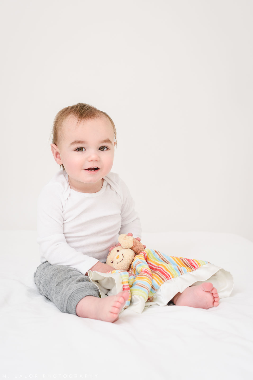 Image of baby sitting with stuffed animal during photo-shoot. Milestone Sessions by N. Lalor Photography. Studio in Greenwich, Connecticut.