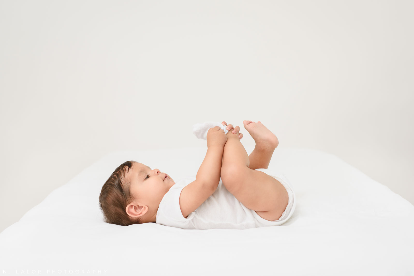 Image of baby in white shirt playing with toes during photo shoot. Milestone Sessions by N. Lalor Photography. Studio in Greenwich, Connecticut.