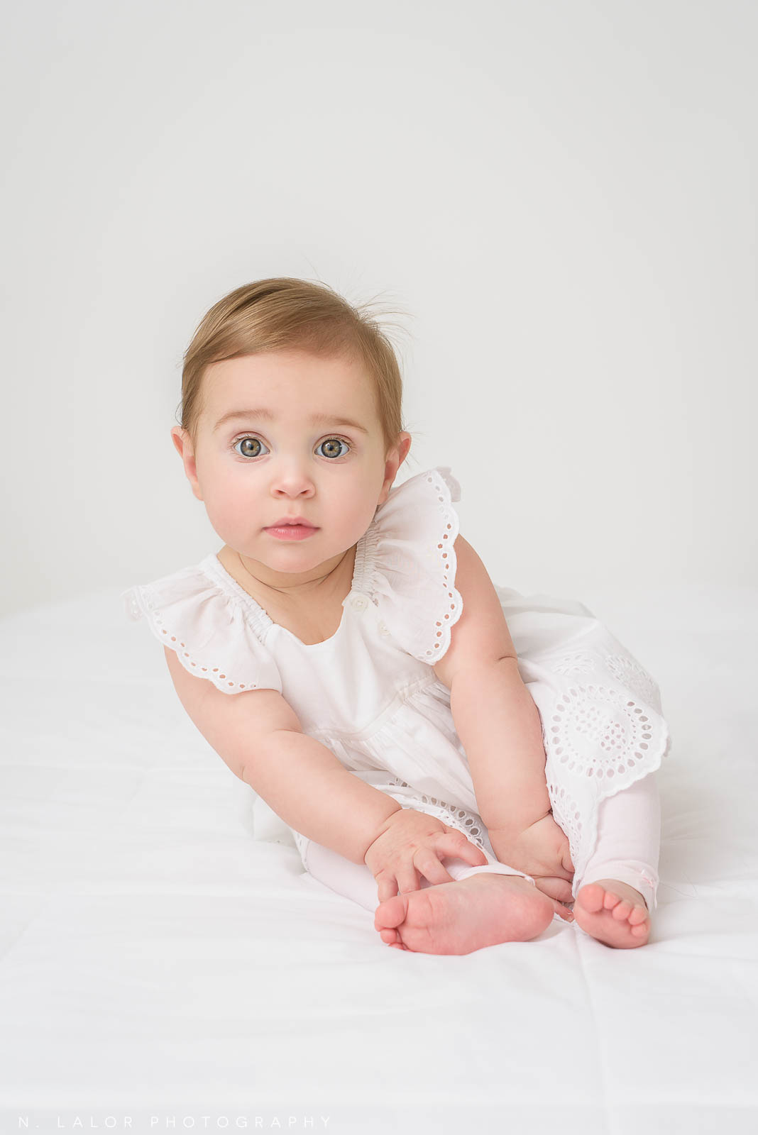 Image of baby in white dress sitting. Milestone Sessions by N. Lalor Photography. Studio in Greenwich, Connecticut.