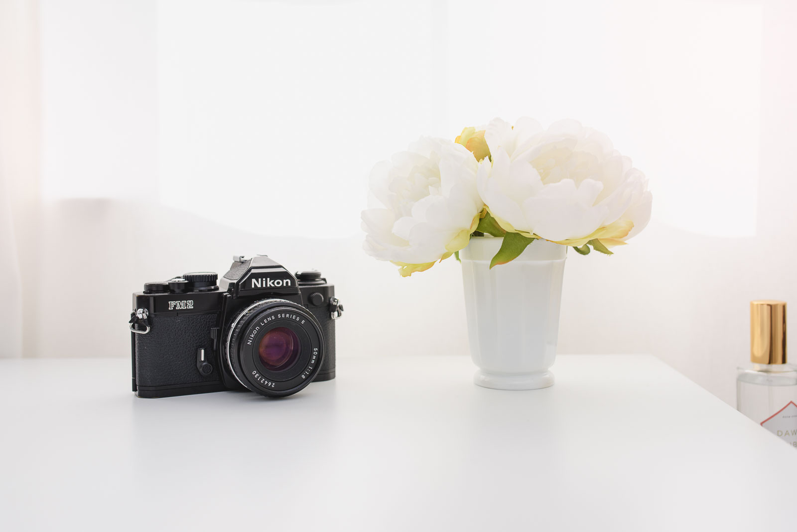 Image of camera and flowers on table. Object photo session by N. Lalor Photography. Studio in Greenwich, Connecticut.