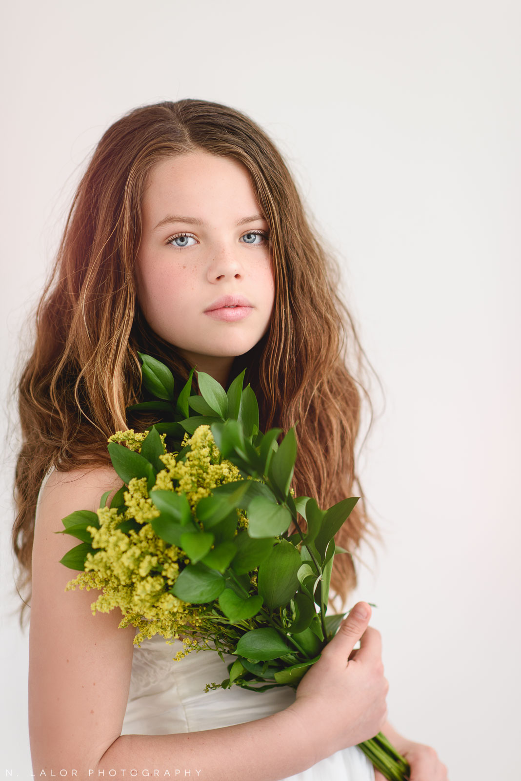 Image of young girl with long hair holding flowers. Photography by N. Lalor Photography. Studio in Greenwich, Connecticut.