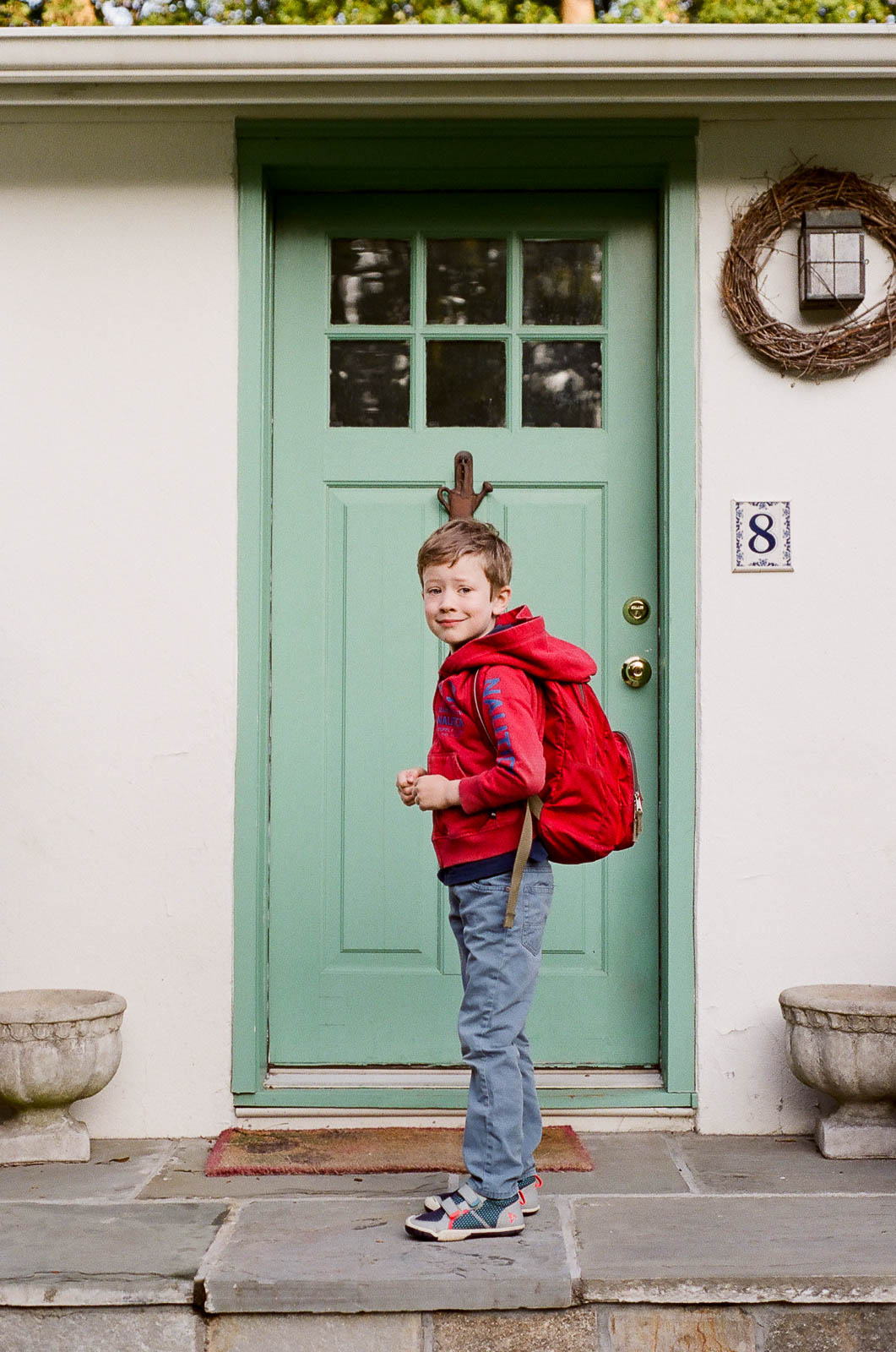 """A photo of Graham on the first day of 2nd Grade. We were renting our house and the bus stop was a 3-minute walk down the street.. so I took this photo before we even left the front steps with my Nikon FM2 to finish out a roll of film. And yes, that is definitely the """"Hurry up Mom!"""" face."""