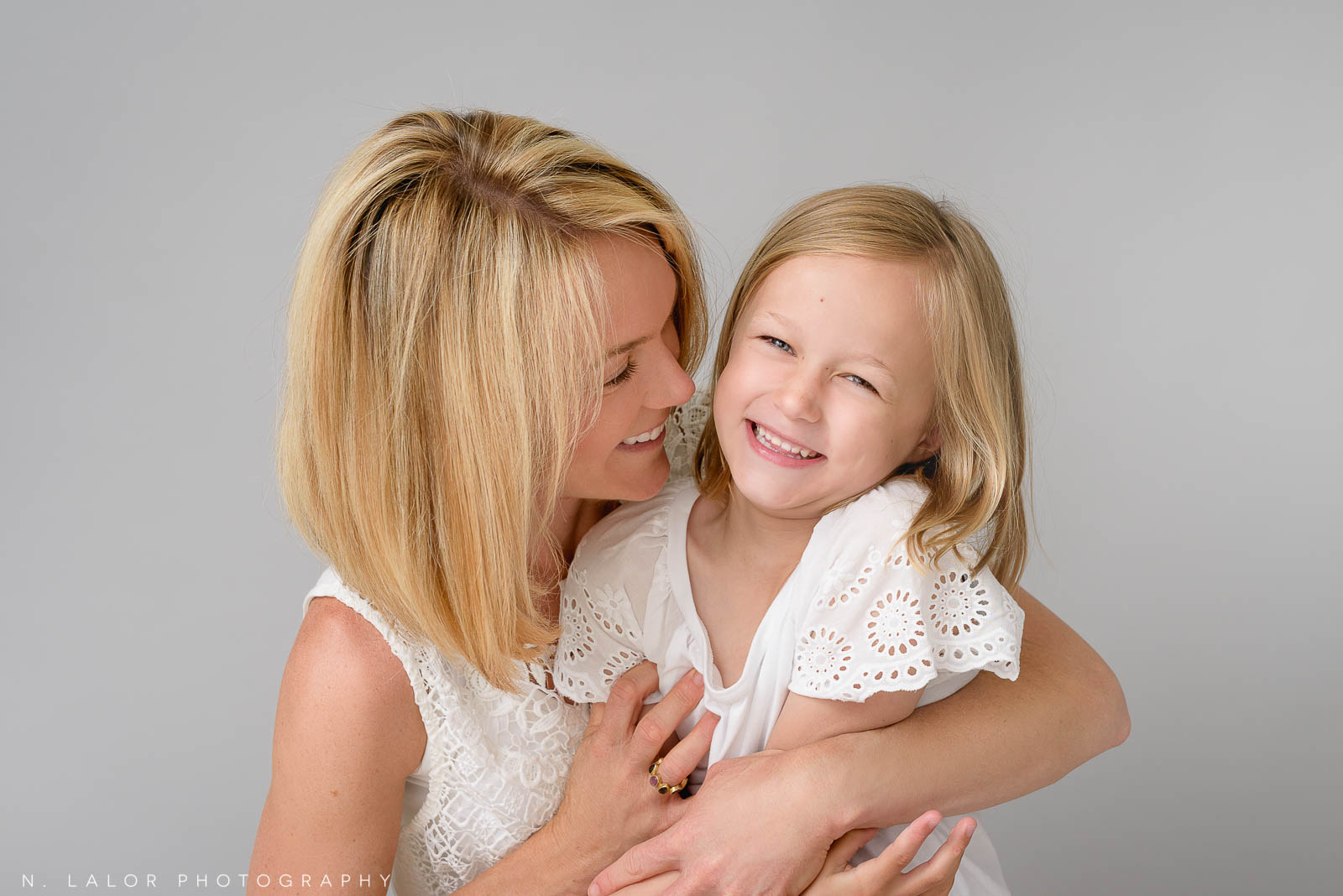 A spontaneous-looking photo between a mother and her daughter. The mother is hugging her daughter close while they both giggle in a shared moment of joy. Photo of N. Lalor Photography Studio in Greenwich, Connecticut.