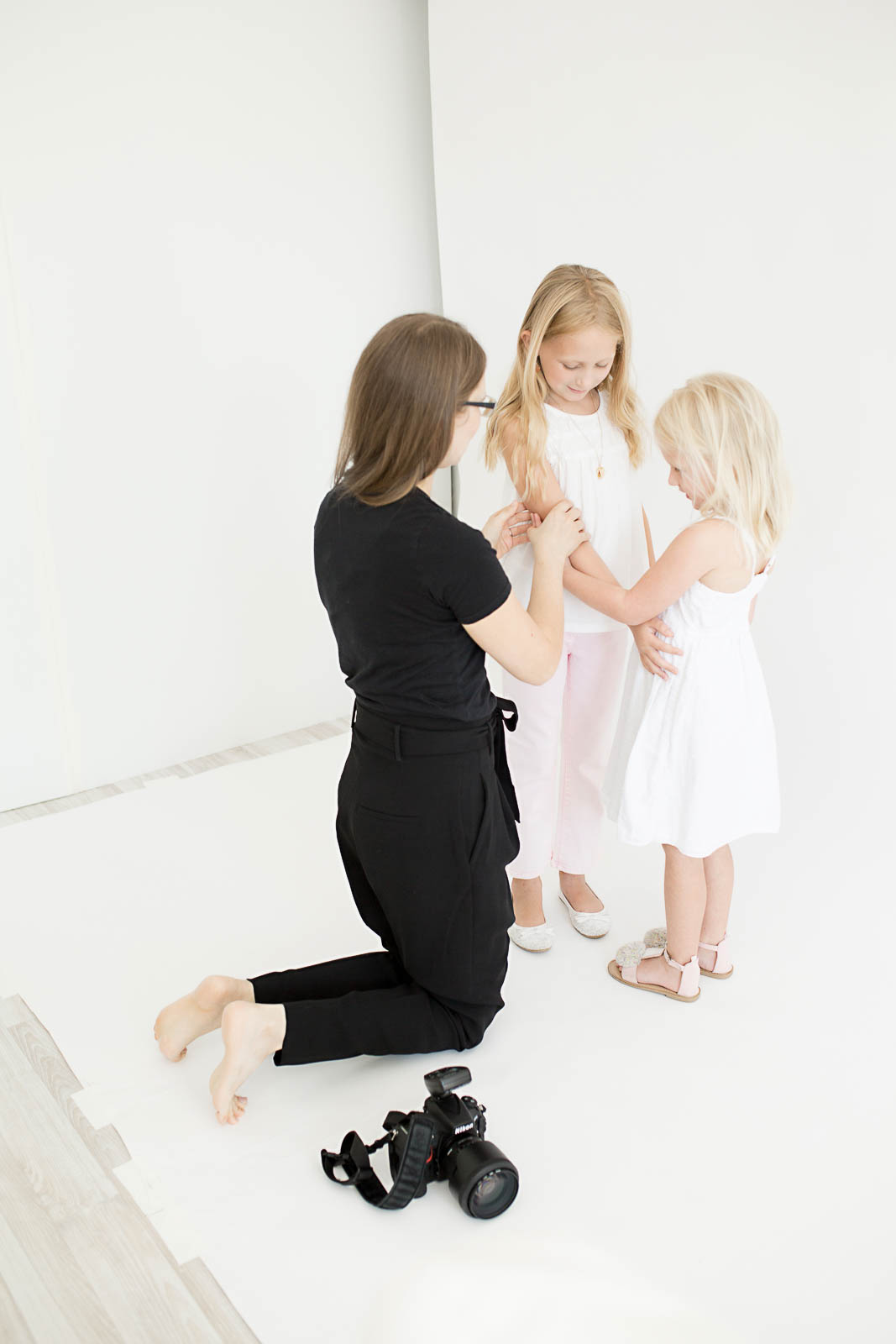 Nataliya Lalor, owner and photographer of N. Lalor Photography, making slight adjustments to the pose of two young girls. Photo of N. Lalor Photography Studio in Greenwich, Connecticut.