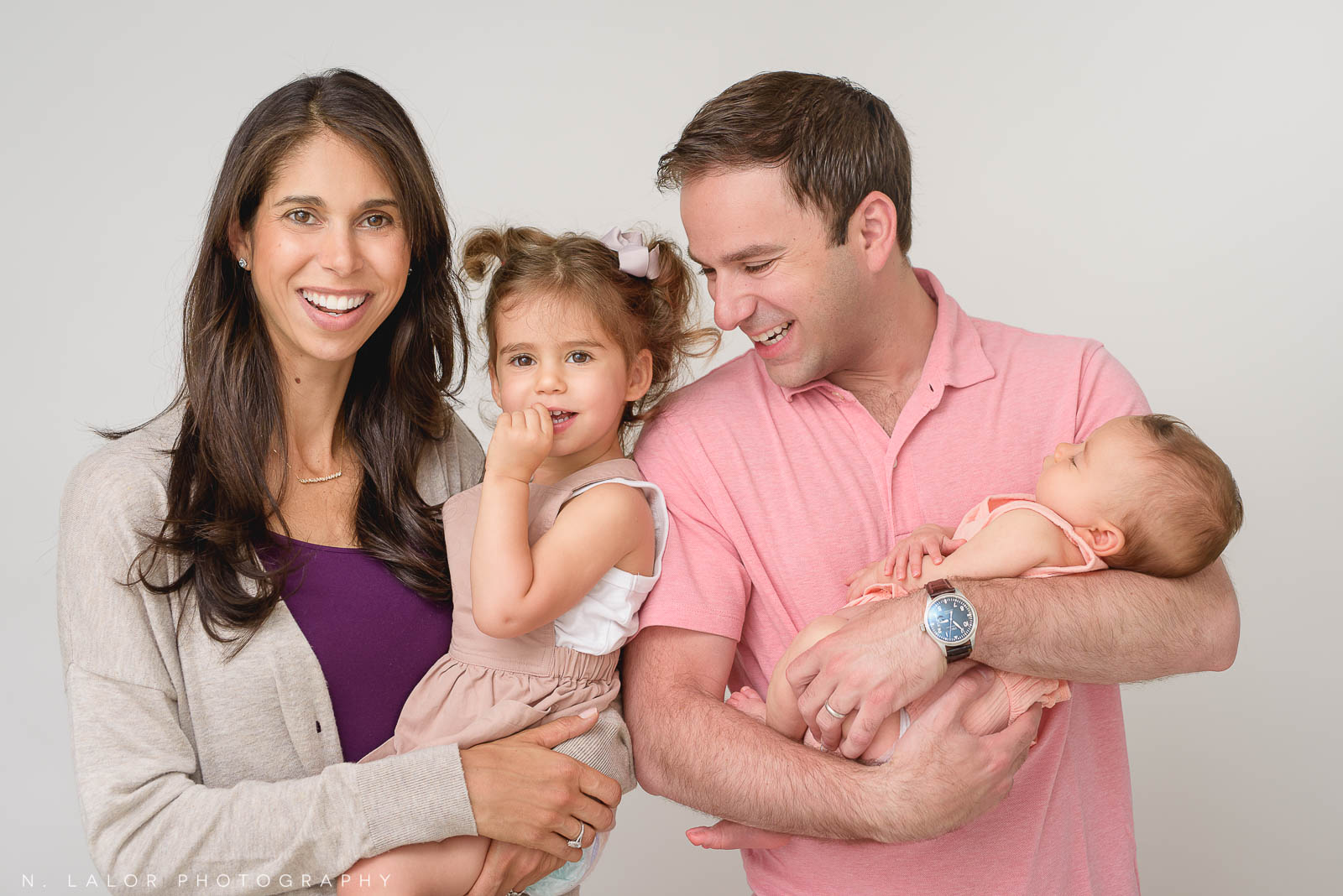Natural-looking family portrait of a couple and their two young children, a couple baby and a toddler. Photo by N. Lalor Photography. Studio in Greenwich, Connecticut.