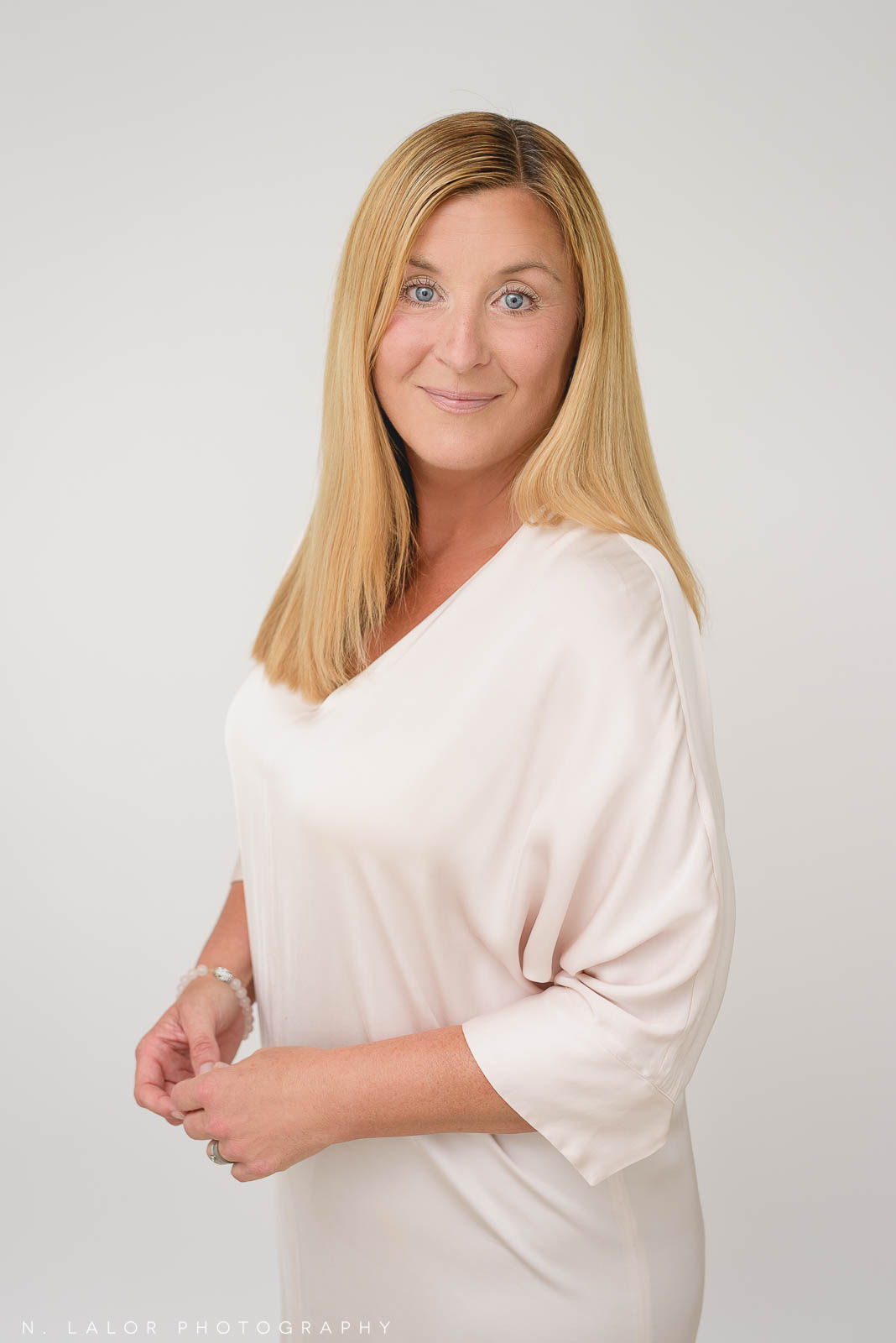 A posed, studio photo of a woman. Her body is tilted away from the camera at an angle while looking straight ahead. She gives off a feminine and friendly vibe. Photo by N. Lalor Photography. Studio in Greenwich, Connecticut.