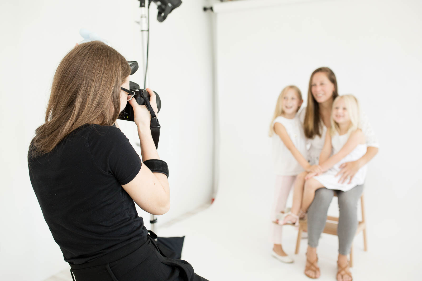 Family photographer taking pictures of a mother and her two girls in a studio setting. Photo of N. Lalor Photography in Greenwich, Connecticut.