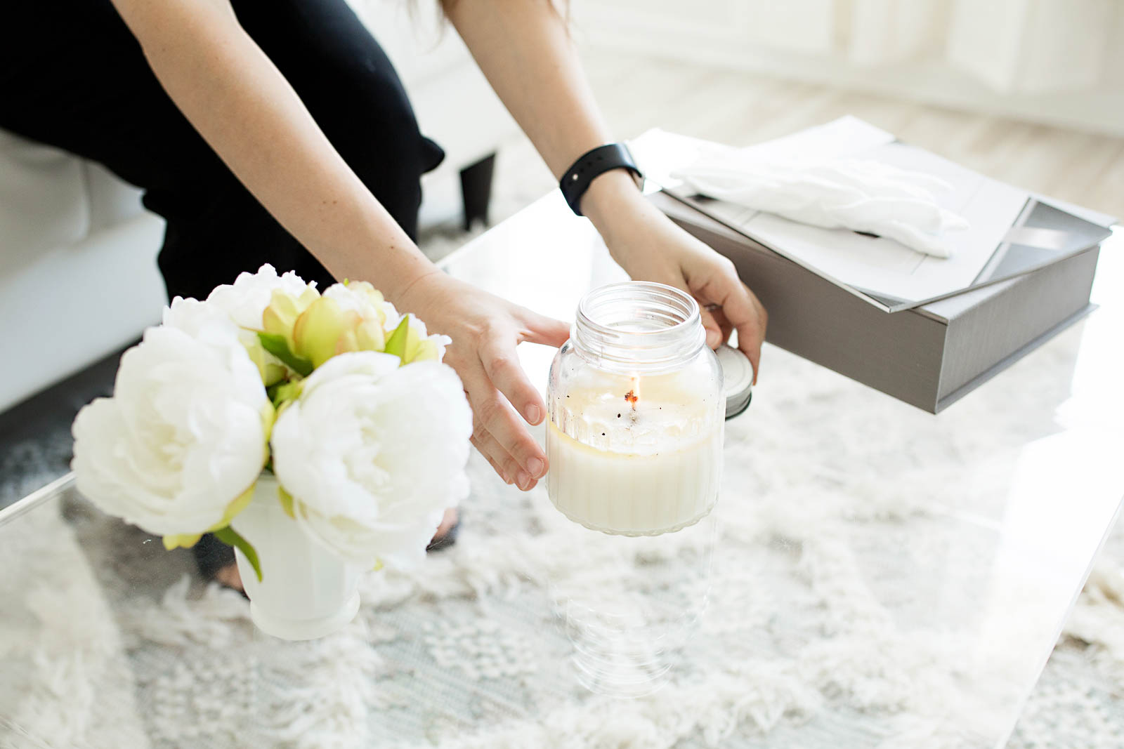 Image of Nataliya Lalor preparing her studio for a family by lighting a candle and setting out flowers. Photo taken in N. Lalor Photography in Greenwich, Connecticut.
