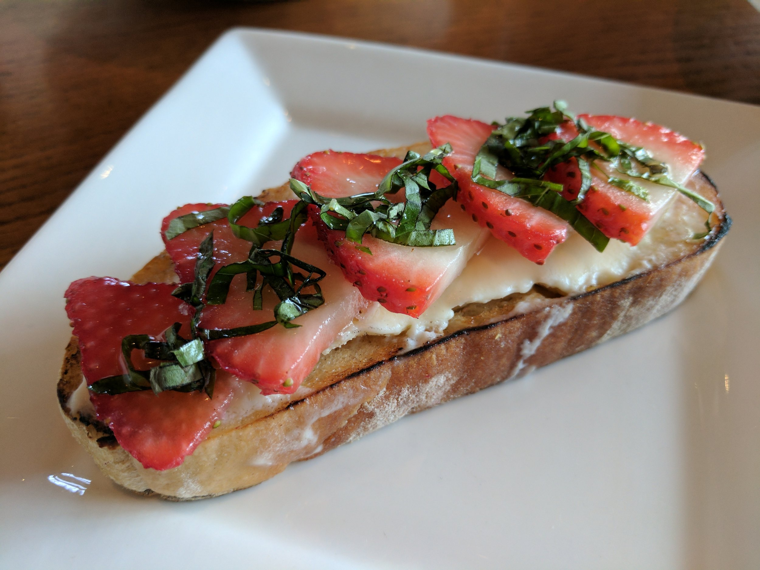 Fresh strawberries sliced over mascarpone cheese, topped with fresh basil and a drizzle of honey.