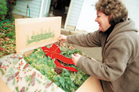 Photo by Flint Carlton Denise Granstrom, owner of Granstrom Evergreens, looks at one of the wreaths created at her Troutdale business.