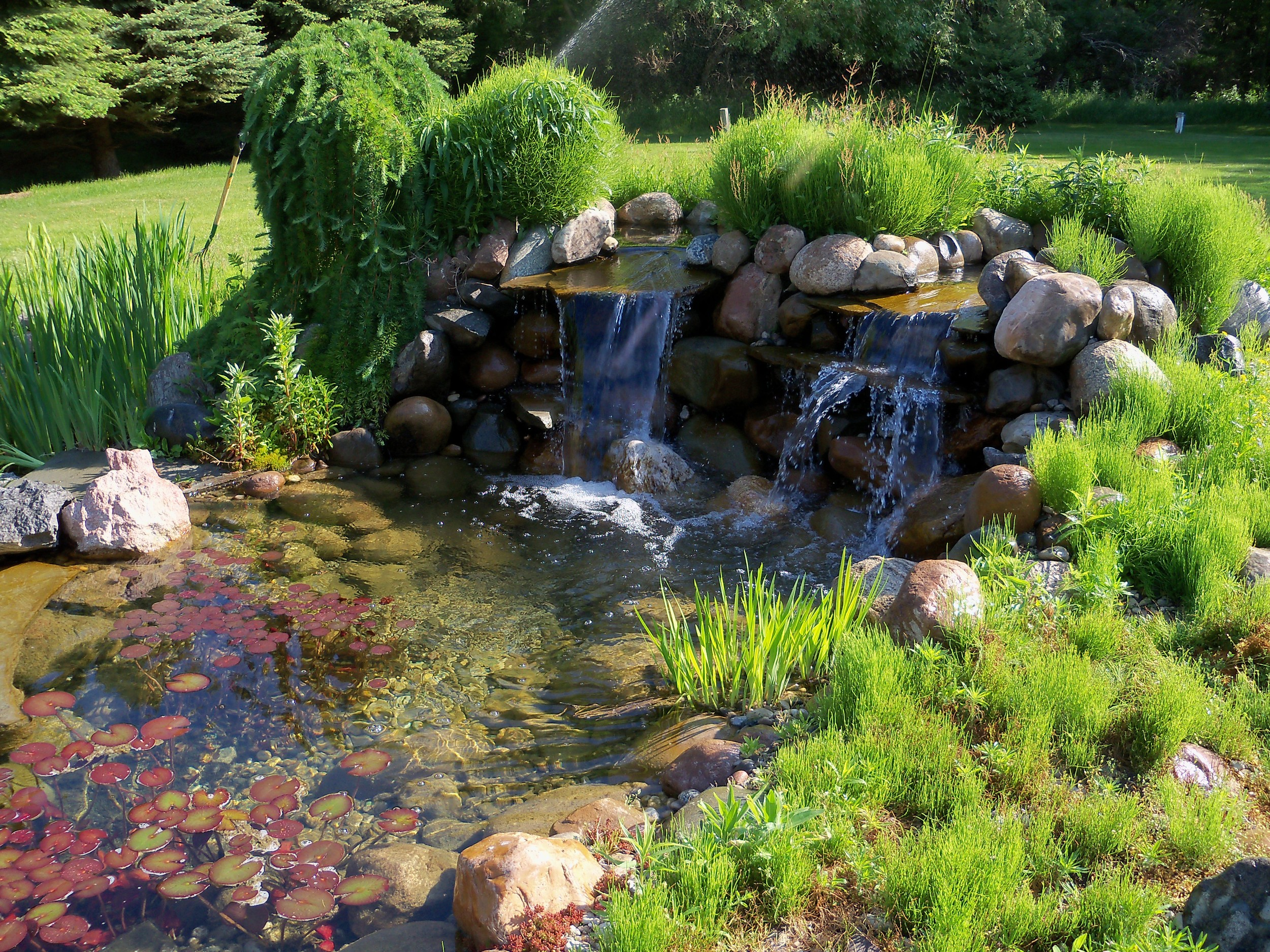 A dual waterfall creating additional ambiance for this pond