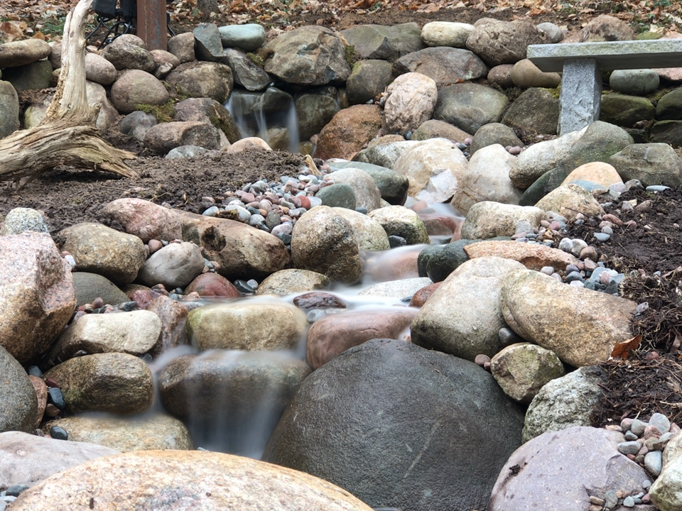 This is the second pondless/pond-free waterfall and stream we built this week. The initial waterfall is followed by a 12' stream. All of this flows into an underground vault we built using Aquablocks.