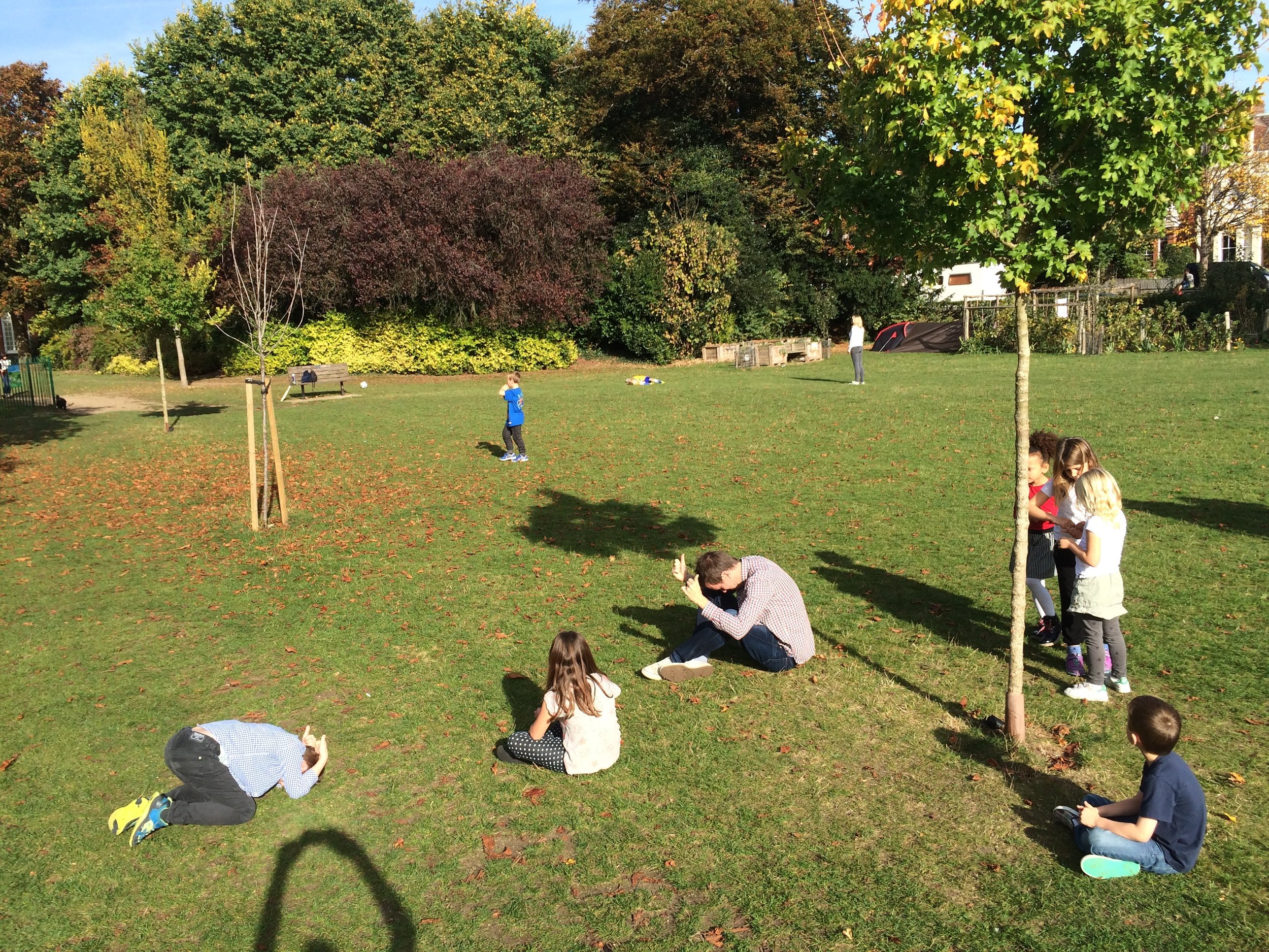 Playing 'Heads down, thumbs up' in the park.