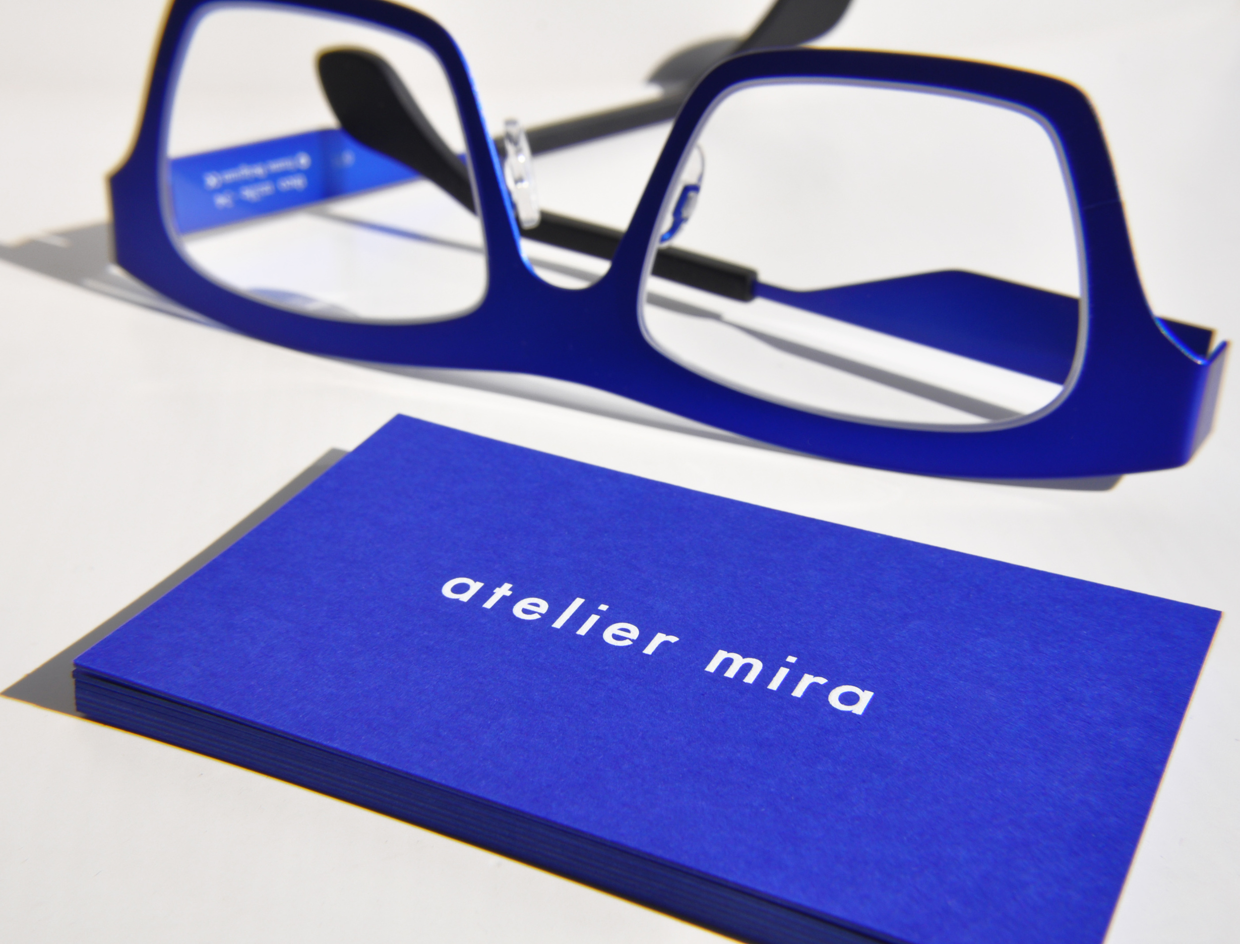 klein blue titanium eyeglasses by Theo Eyewear with business cards from Atelier Mira