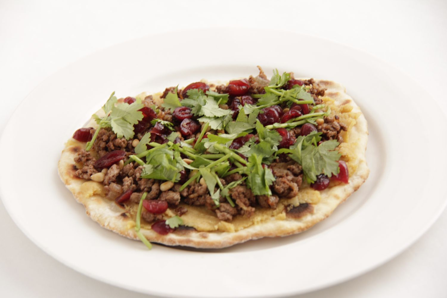 Home made flat bread used to make Middle Eastern pizza with lamb and cranberries for one