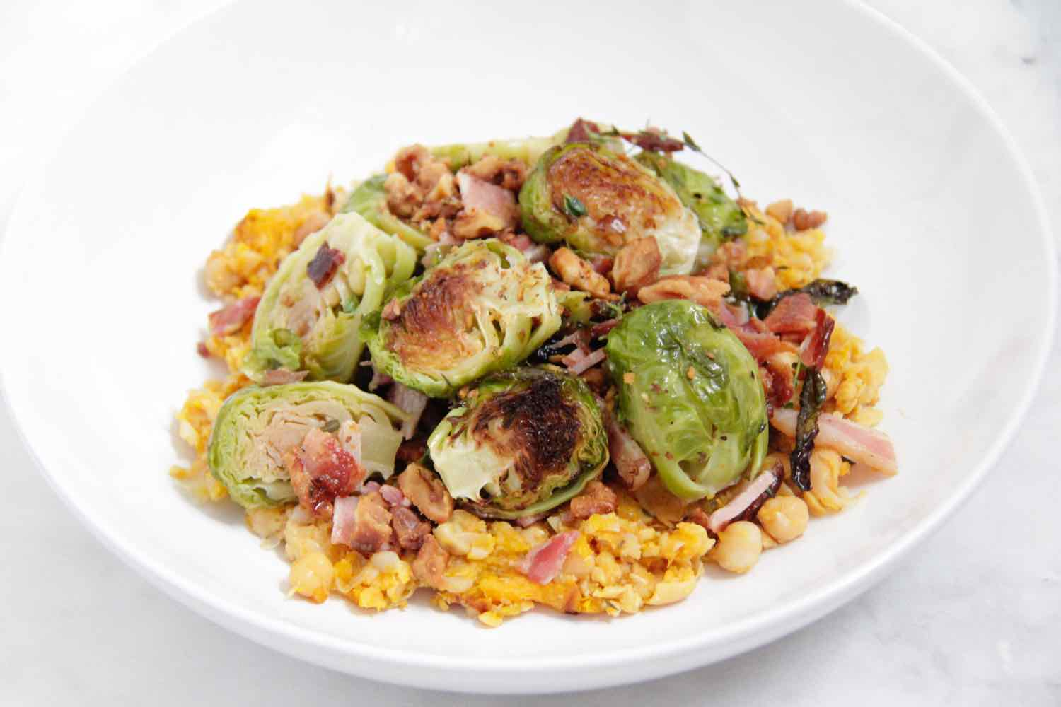 Brussel sprouts roasted with lemon and pancetta and served on roast pumpkin / chickpea / cumin smash