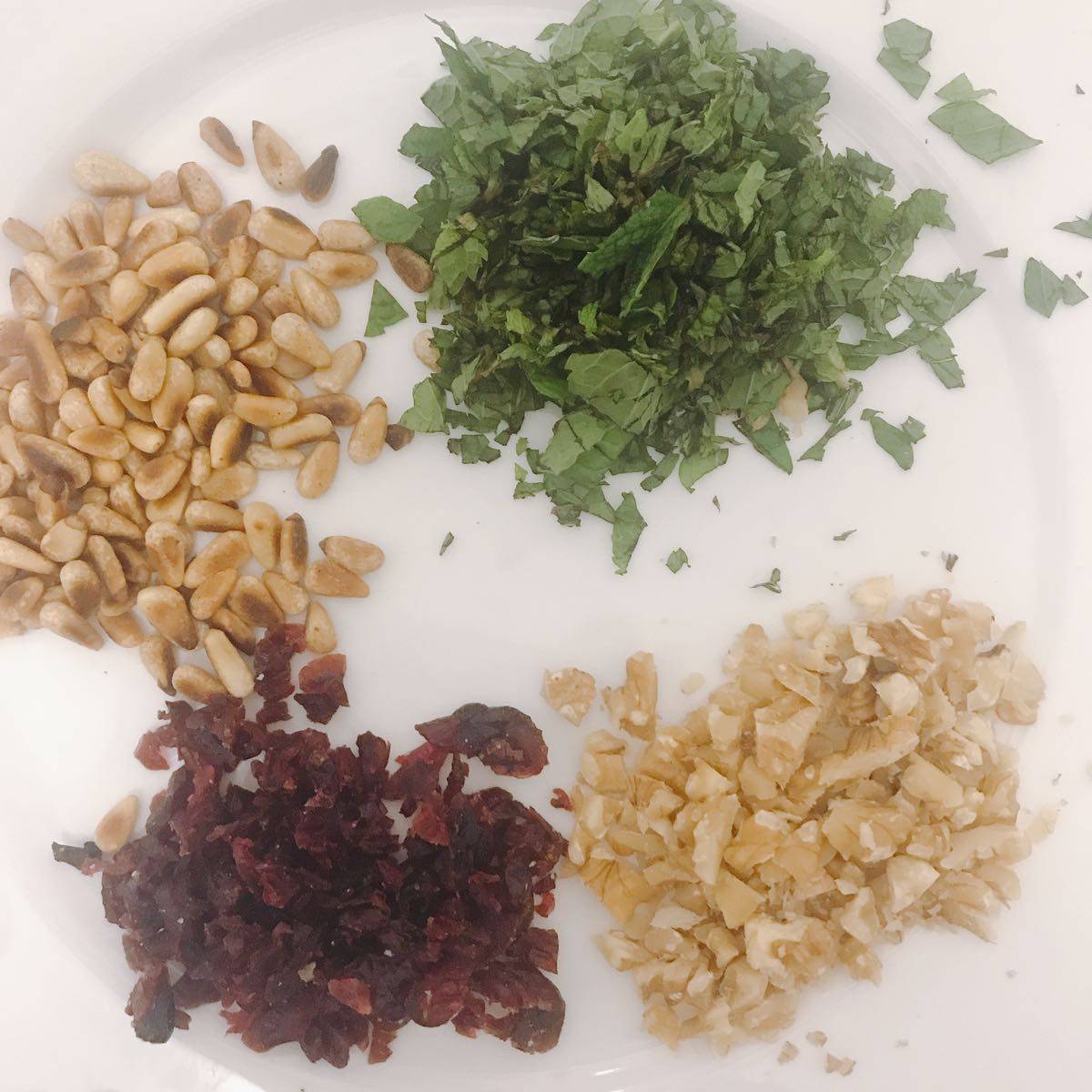 Step 2, chop and prep ingredients for the toppings and salad. Mint, pine nuts, walnuts and cranberries.